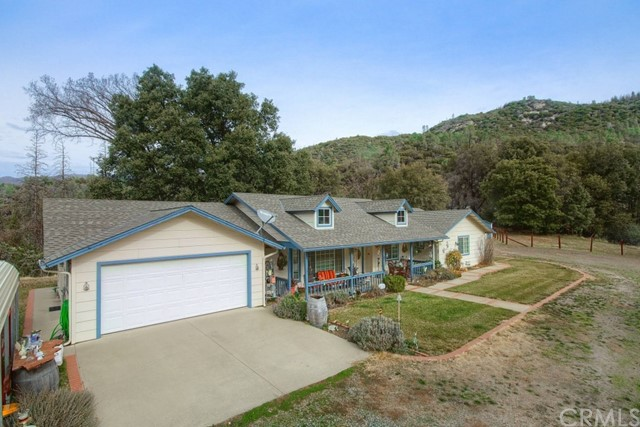 If you are looking for a place to call home, living in peace and serenity with beautiful pines, oaks and cedars and close to both Mariposa and Oakhurst, look no further! This home is a dream come true! Gorgeous private setting with panoramic views, year 'round creek and plenty of room for horses. This 2135+/- sq. ft. 4 bedrooms, 3 bathrooms has separate living room and family room, with built-in book cases, open kitchen, separate spacious laundry room, tile floors throughout, free standing wood stove, large covered porch in both front and back with outdoor ceiling fans, plus appx. 600 sq. ft. steel building with bathroom, possible guest home, permitted as storage, all on 5.5+/- acres with 2800 elevation.  Includes a large fenced-in orchard with apple, plum, apricot and pear trees. 2 Tuff sheds, chicken coop, full RV hook-ups. 2 car garage plus carport.  Enjoy the evenings, watching the moon come up and shooting stars!