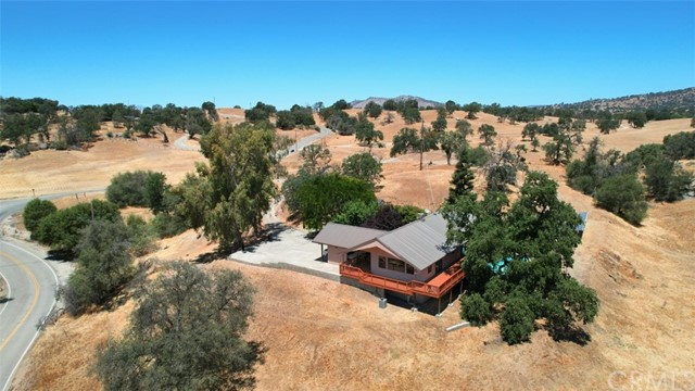 Dream home in the Clovis Foothills. Are you looking for a large and spacious family home in a peaceful setting? How about 360 degree views? Well this may be the one! Beautiful custom 2900+/- sq. ft. home with 4 bedrooms, 3 bathrooms sits on just over 9 gorgeous all usable acres. Impressive kitchen is open to the living room and family room.  Remodeled in 2011, truly a cook's delight with plenty of room to entertain from with 3 ovens, trash compactor, dishwasher, self-closing cabinets, RO system, water softer, recessed lightening, 2 breakfast bars, and rolling island. Separate dining area. Master bedroom and bath are on the main floor along a guest bedroom. Living room has a large rock fireplace, surround sound throughout, walk down to the second level for additional 2 more bedrooms, living room and large bathroom with walk-in shower. The outdoors is inviting with a built-in swimming pool. There is plenty of room to build a shop or garage. Private wells, sprinklers and drip systems. Home has solar, new AC and heating unit. Wait there is more, metal roof, stucco siding, 2 car carport and the entire property is fenced. Just 20 minutes from Clovis. Did I mention the views!  This spacio