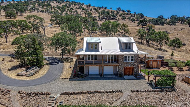 A craftsman-built home with artist-attention to detail at 1200' elevation on 5.61 acres sits above an organic family vineyard that has been producing fine foothill Barbera since 2012. Enjoy the covered porches, grape arbor, and walled courtyard. Expansive views of beautiful rocky hills, the valley below, and the coast range beyond can be seen from 48 windows on three levels. Surrounded by oak and hillside pastures with seasonal creeks, it offers privacy and seclusion yet is only minutes away from three recreational lakes with an easy commute to Modesto, Merced, Turlock, and Sonora. UC Merced is 30 minutes down the hill. Yosemite is 90 minutes up the hill. This solid home features post and beam construction, tongue-and-groove vaulted ceilings, concrete counters, gourmet kitchen, walk-in-pantry, bamboo/tile floors, tile showers, spa bath in master suite, large shop, oversized garage, and wine cellar. This home is listed as a 2 Bedroom, 4 (2 2) Bathroom.  However, there is also ample space for an additional bedroom in the large bonus room or in the finished shop area at garage level where one of the half-bathrooms is located.