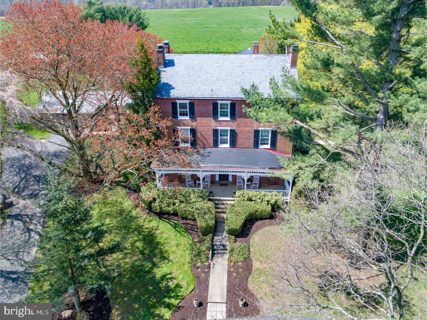 Welcome to Twin Chimneys, Circa 1762!  This stately historic Federal style home has three main periods of construction and sits high with sweeping vistas.  The original stone two story farmhouse was built in 1762.  Many historical accents such as the original kitchen and over sized fireplace and bee hive oven remain and add to the historic charm.  In 1880 the three story brick Federal house was added and includes the grand central foyer entry which features a grand staircase that takes you up three floors.  The bricks for this part of the house are hand-made and were kilned on the property near the large sycamore tree that is by the White Clay Creek that wanders through the property.  The twin brick chimneys as well as multiple fireplaces were a necessity back then, and still adorn the home today.  Without compromising the original structures, the current owner added the Great Room and gourmet kitchen in 2008.  The Great Room features walls of windows and doors with views and access to the tiered stone patio, pool and hot tub area.  The original outside stone wall remains and adds a wonderful backdrop accent wall that matches the new stone floor-to- ceiling raised hearth gas fireplace.  This magnificent home boasts classic exceptional features throughout including deep window sills, original support timber with square nails and some of the original cabinetry throughout the home.  Beautiful wide plank pine flooring and radiant heat were installed on the first level.  Spacious