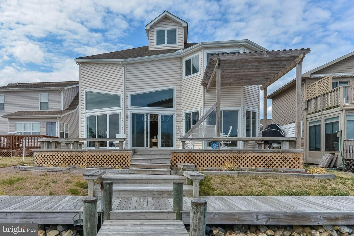 NO CITY TAXES! Priced Reduced! Luxury Coastal Contemporary Bayside Waterfront Living at 13461 Madison Ave. North Ocean City. This Custom Built High Quality Construction Home was Built as a Builders' Personal Residence with panoramic water views and private dock with boat lift. Plenty of natural light flows throughout the home's open, airy layout. Generously-sized living/dining area with gas fireplace for family gatherings graced by huge windows and glass sliding doors that lead out to the rear decks. The sprawling entertaining spaces flow outside to the multi-level sun decks and tranquil premier bay front. First-floor MASTER suite offers built in dressing table and en-suite tile bath with soaking tub. Upstairs has guest rooms with private bath plus huge 3rd floor bonus room with OC skyline views!