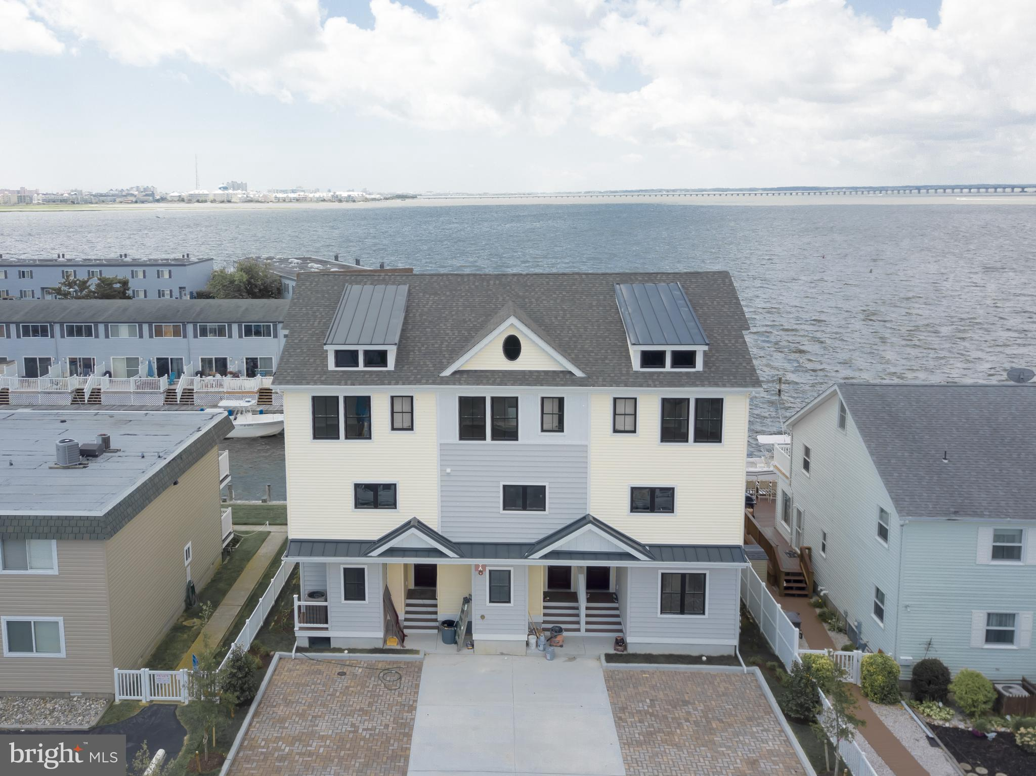 This is a must-see custom designed, new construction 3 b/r 3 1/2 bath beauty! First floor offers a bayfront bedroom, full bath and laundry/utility/storage room. Second floor has wood laminate floors throughout the open floor plan, bayfront living area, kitchen w/ SS appliances, granite, large breakfast bar & powder room. Third floor boasts two master suites, bayfront b/r has sweeping panoramic views of OC, bay & Rt 90 bridge. Each unit has two assigned  parking spaces with two bonus spaces to be shared among 3 owners. Seller is under contract & permits are in process to replace bulkhead at sellers expense as well as to install pilings for elevator lifts for both  A & B units.  Buyers will be responsible for purchase of the actual lift but i