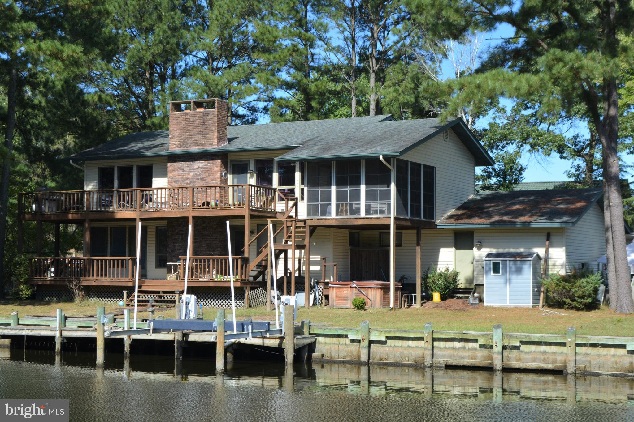 Unique waterfront home overlooking the 10th tee of the Ocean Pines golf course.  Spacious decks and 3 season porch have gorgeous views of both the waterway and fairway.  The home has a large 1/2 acre yard and over 200 feet of bulk-headed waterfront with dock and boat-lift. Two open living rooms, each with its own wood-burning fireplace and two master bedrooms, can accommodate your guests. Upgraded kitchen and dining room have brilliant views of the waterway and golf course. Downstairs living room includes a wet bar for entertaining.  Hot tub, outdoor shower and garage with workbench. Encapsulated crawl space with dehumidifier. Dual zone HVAC. 1 year HMS Home Warranty