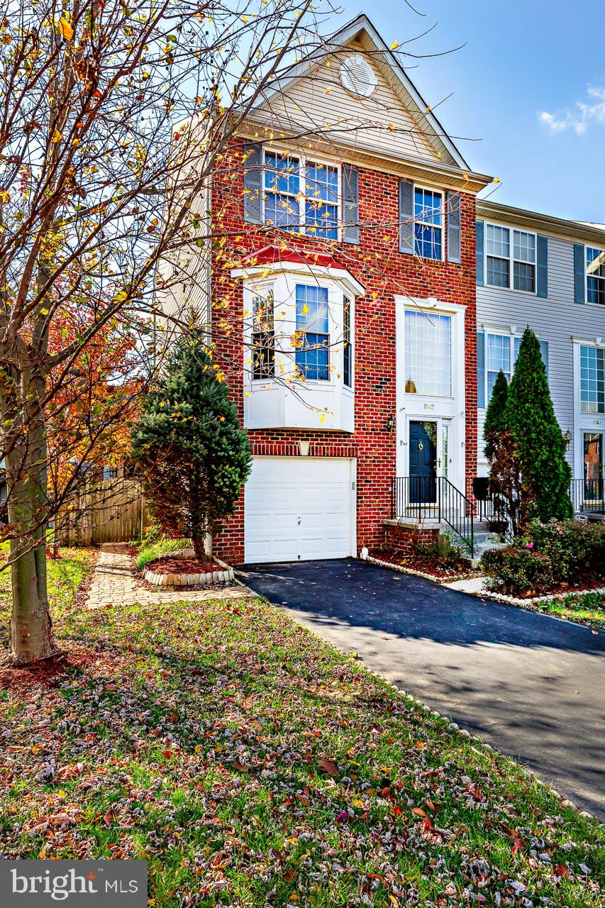End unit townhouse with brick front and 3-level bumpout in North Crossing adjoining open space and p
