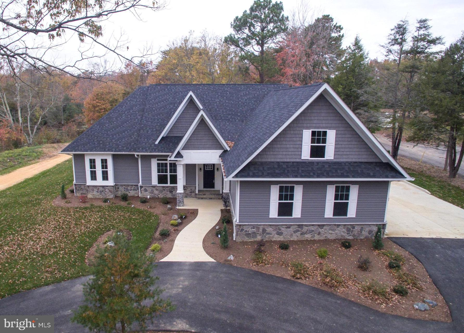 Stunning custom built home is ready for the Holidays! Nestled back from the road, accented with ston