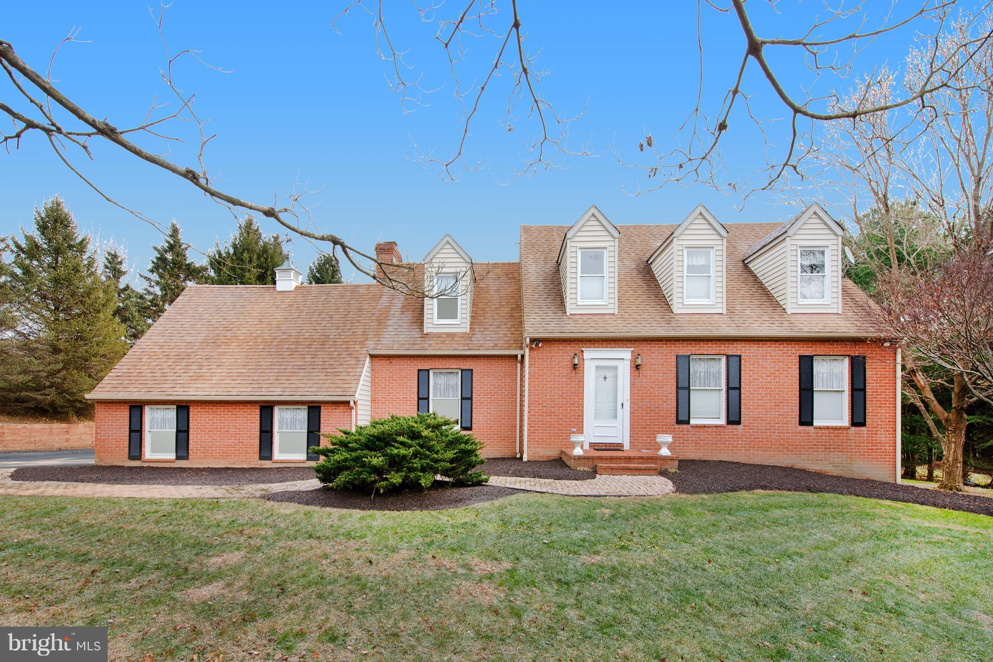 Beautiful brick-front cape cod home nestled into cul-de-sac setting and sitting on just over one acr