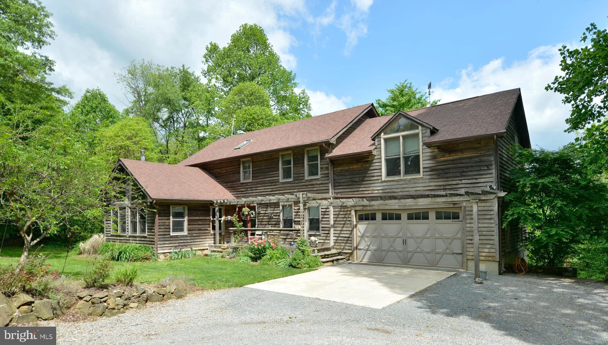 What a setting!  Private - wooded 5 acre park like setting with Western Valley views. Cedar sided be