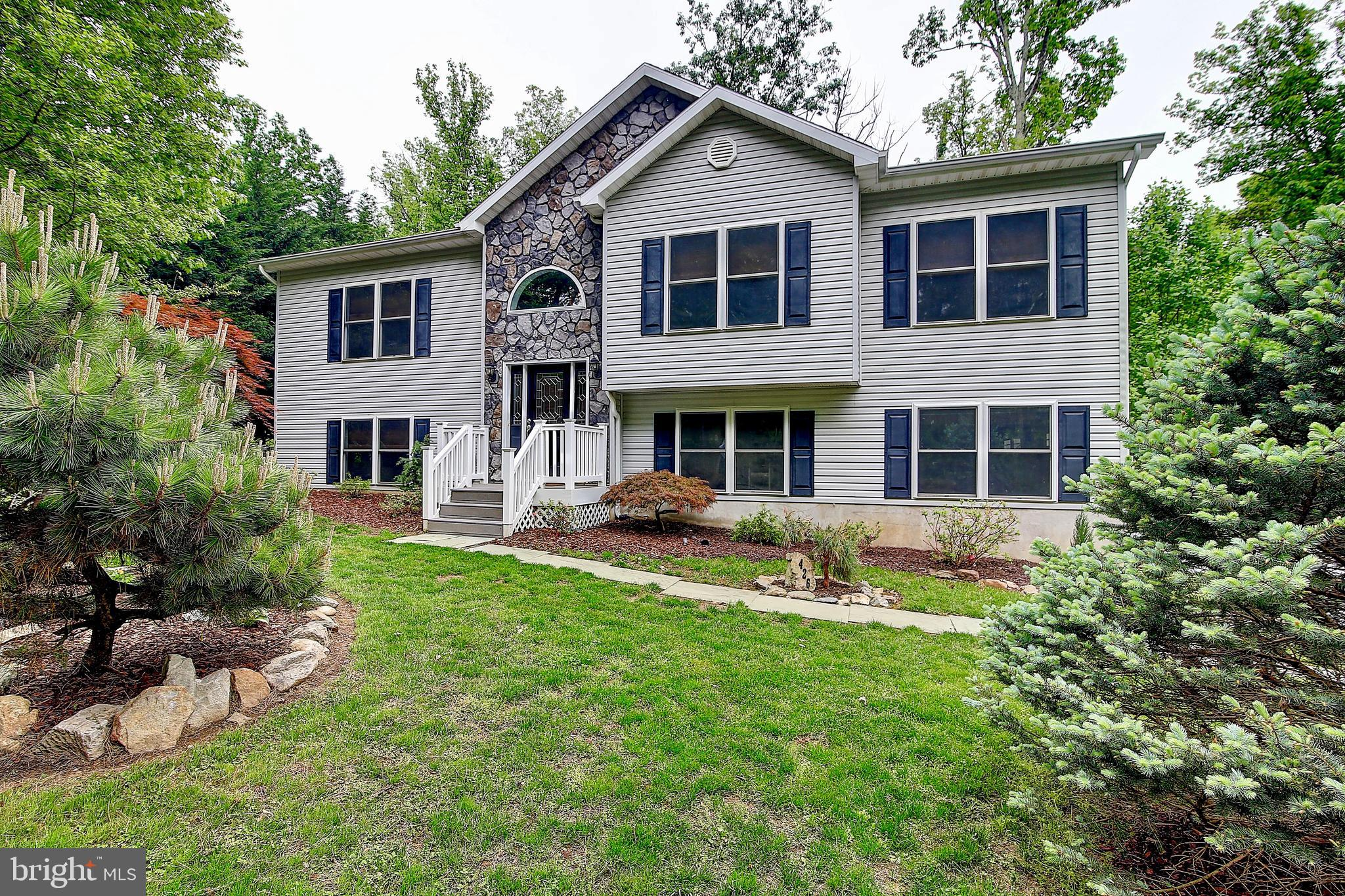 Enjoy serene forest views and plenty of privacy in this immaculate, beautiful split-level contempora