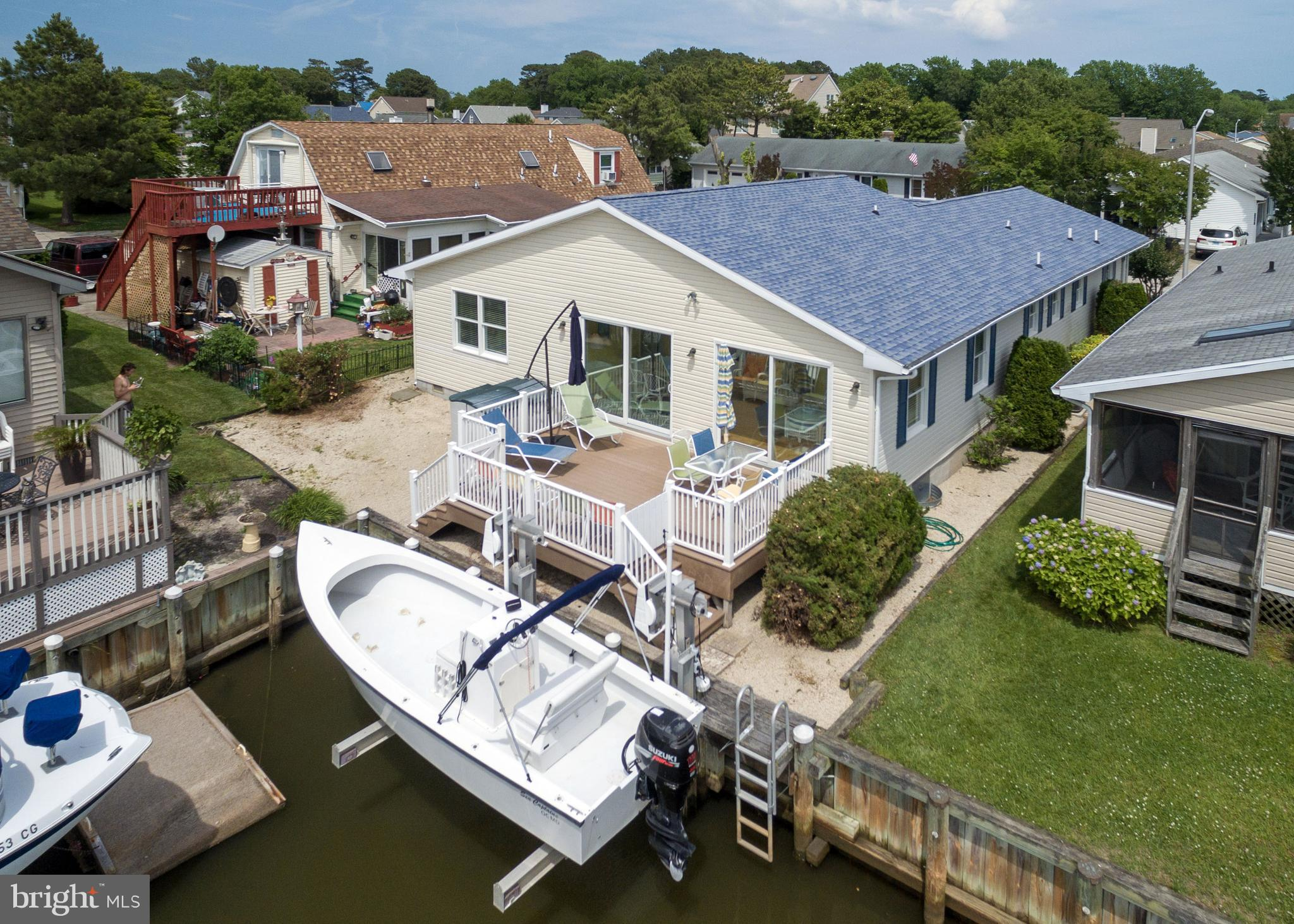 BAY FRONT LIVING IN THE SERENE COMMUNITY OF CAINE WOODS WITH PRIVATE 5,000 LB BOATLIFT! Great multifamily beach home has an expansive floor plan with fantastic views of the Assawoman Bay from several rooms. Both queen sofas are sleepers and the bunk beds have trundles, so there is plenty of space for all!  Boast 5 bedrooms and 4 full baths, two master suites, with one being bay front and a junior master w/ attached bath.  Relax in the bright and over sized sun room with 2 upgraded 9' Anderson Storm sliding doors providing plenty of natural light to shine through. The kitchen has upgraded Silestone counter tops,  stainless steel refrigerator, corner kitchen island seating,  and a breakfast nook. Spend the day soaking up the sun on the grand bay front  rear deck in the telescope chairs & lounges that convey, or head to beach only a short drive away.  Covered carport has room for 4 mid-size vehicles as well as plenty of off street parking. Very low maintenance yard, poly crawl space in good condition, and the  storage shed conveys! This location is quiet and family friendly, great for walking or riding bikes, and has it's own dog park. Option to purchase boat with new trailer, ask agent for details.  Pride of ownership is immediately noticed as you step inside, call to make your appointment to see for yourself!