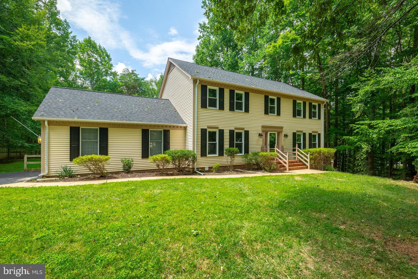 Beautiful Colonial on wooded 1+ acre lot! Hardwood floors & custom molding detail throughout main le