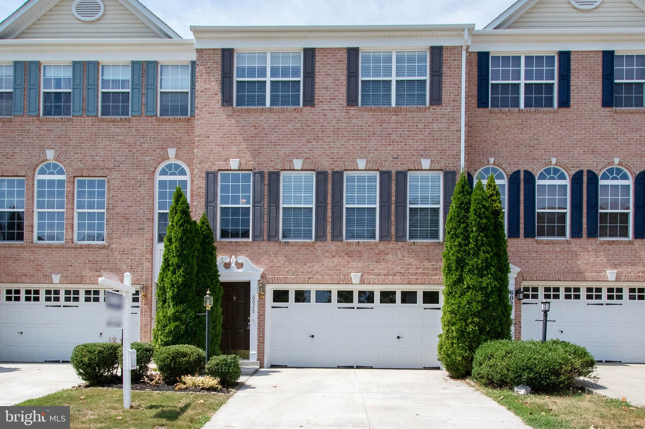 Sunlit TURN-KEY 3BR/2.5BA townhouse with STATELY brick front, 2-CAR GARAGE & ALL levels finished in