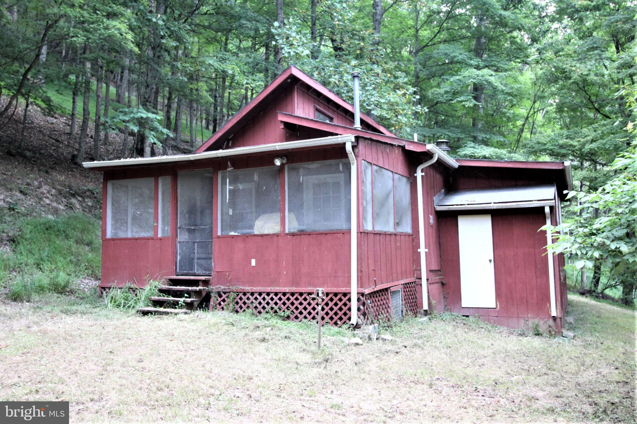What more could you ask for? This darling red cabin with two bedrooms, full bath, galley kitchen, living room and dining room is on over 4 1/2 wooded acres! Located in a recreational community that surrounds the 44 acre state owned, maintained and stocked Warden Lake! Enjoy an evening by a camp fire listening to the soothing night sounds or curl up with a good book on the enclosed screened porch. Not only can you enjoy the pleasure of Warden Lake but, you can go to the quant shops, farmer's market & restaurants in the Town of Wardensville, just 5 minutes away. Approximately 2 hours from the DC area and 40 minutes from Winchester, VA.