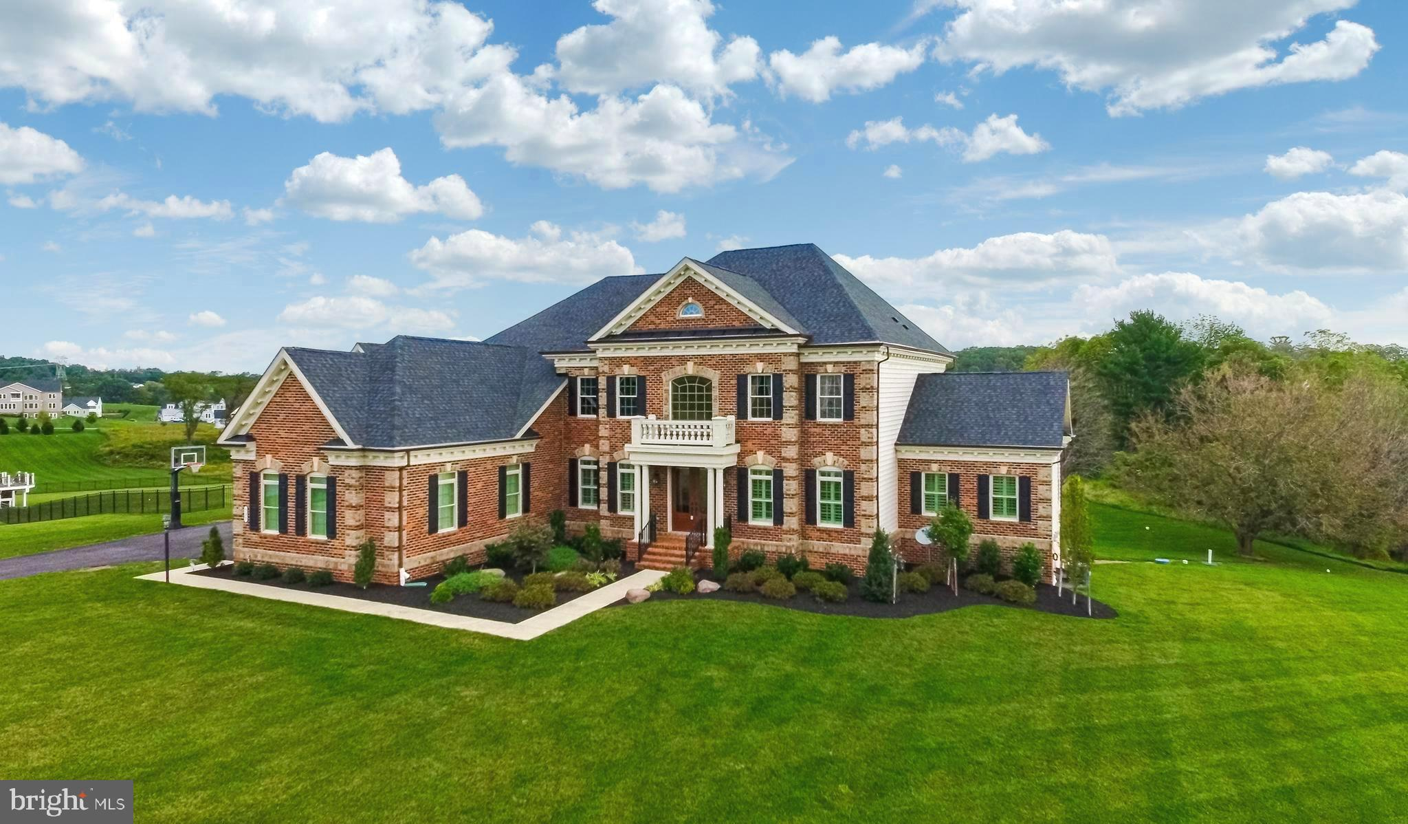 This Magnificent and Stately All Brick Colonial Perfectly Placed on a Lush 2 Acre Lot with Attached