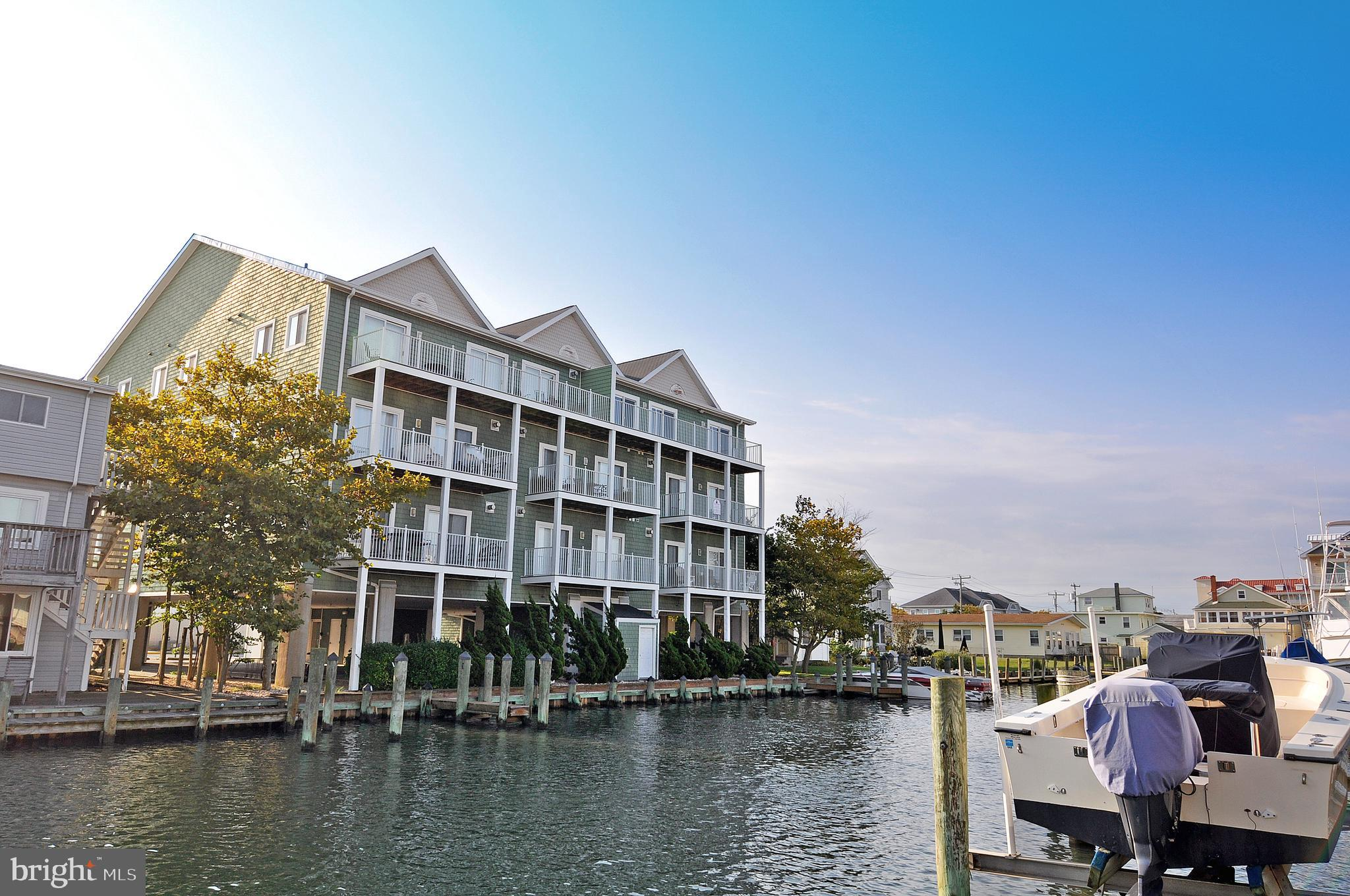 Beautiful 3 bedroom 3 bath bay side waterfront condo within a 3 minute stroll to the beach and boardwalk!~ Featuring many upgrades including gas fireplace, stainless steel appliances, storage closet, separate laundry room with shelving,~ ceramic tile floors & hardwood floors, granite counters, spa tub & more.~ The building has covered parking, community docks, outside shower, elevator, bike storage and secure lobby entrance. Watch sunsets from your rear private balcony or the air show from your front porch.~ Great 2nd home or could make fantastic rental.~