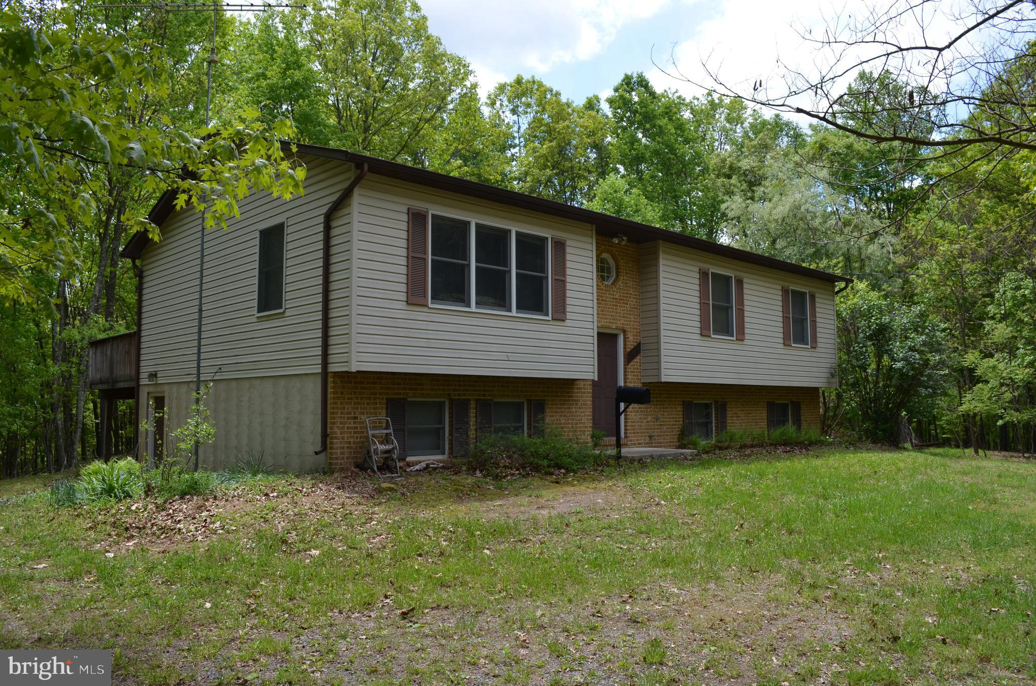 Nestled in the woods is this 3 bedroom, 2 bath home with new flooring throughout. Large deck off of