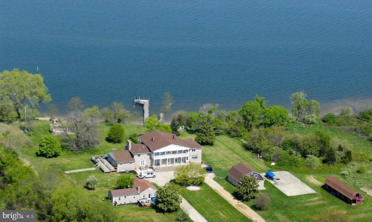 Fantastic Waterfront Opportunity! 12.44 acres zoned commercial marine on Breton Bay ~ Main house currently divided into 3 units but can easily be converted back to one house with an in-law suite ~Tenant house/cottage house has 2 bedrooms, 2 full bathrooms, kitchen, laundry and great room ~Tenant house and in-law suite have been renovated ~Two-car detached garage with walk-up steps to attic storage or possible workshop ~ Open shed for boat storage, equipment and more ~ Private pier with deep water ~ Perfect for a large family needing an in-law suite and/or a second residence ~ Commercial uses such as bed & breakfast, marina & marine-related sales, boating clubs or associations, special event location and so much more!  Allows over 100 boat slips and land for a boatel ~ The possibilities are endless with this gorgeous property.