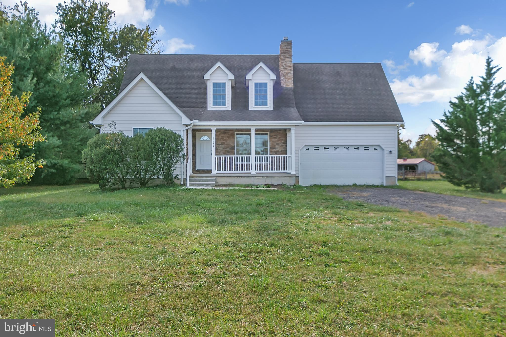 Lovely Cape Cod with front porch, 2-car garage,  deck, fireplace and unfinished basement. House is i