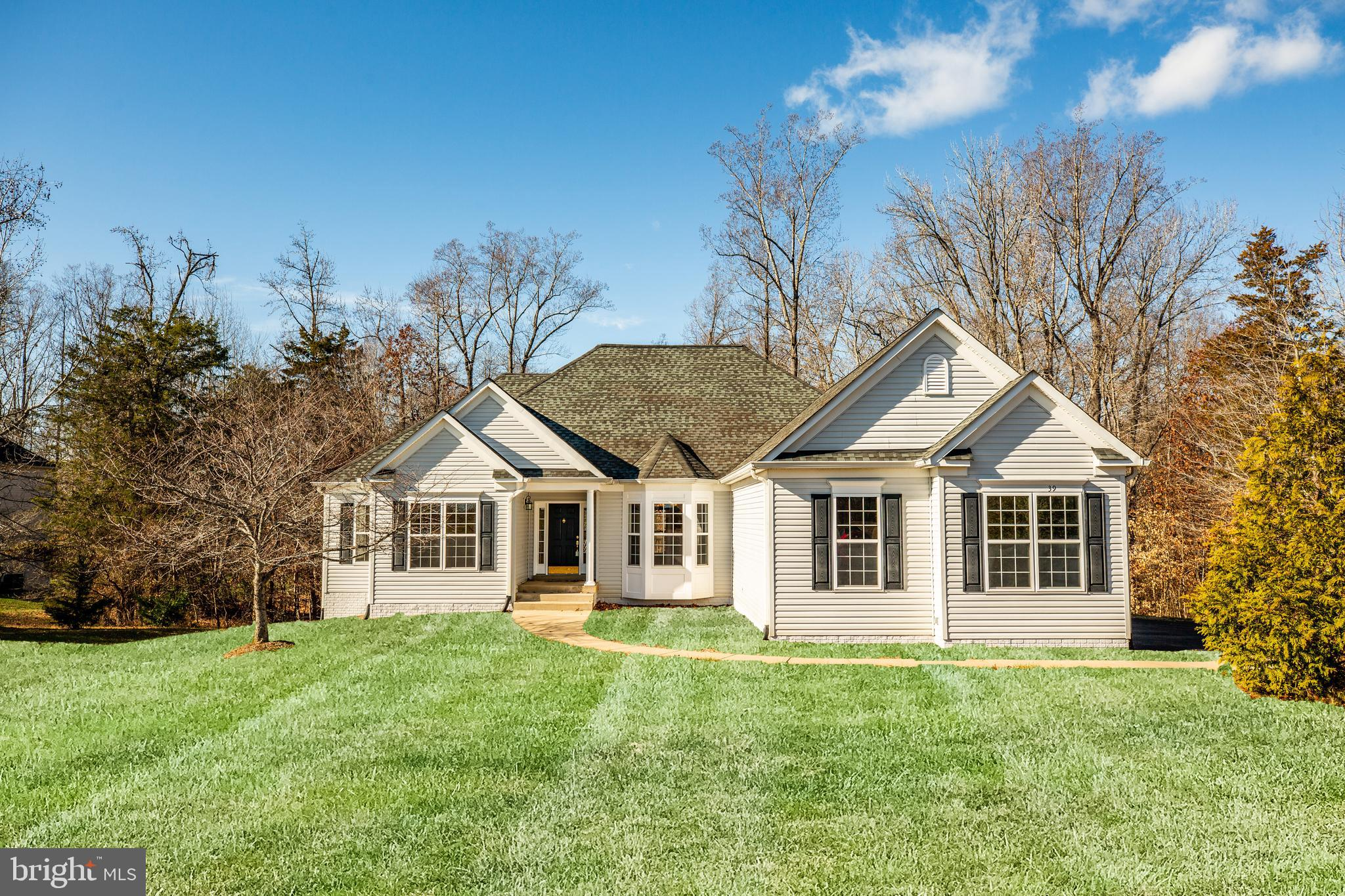 Welcome home to this immaculate custom rambler with main level living on three private acres backing