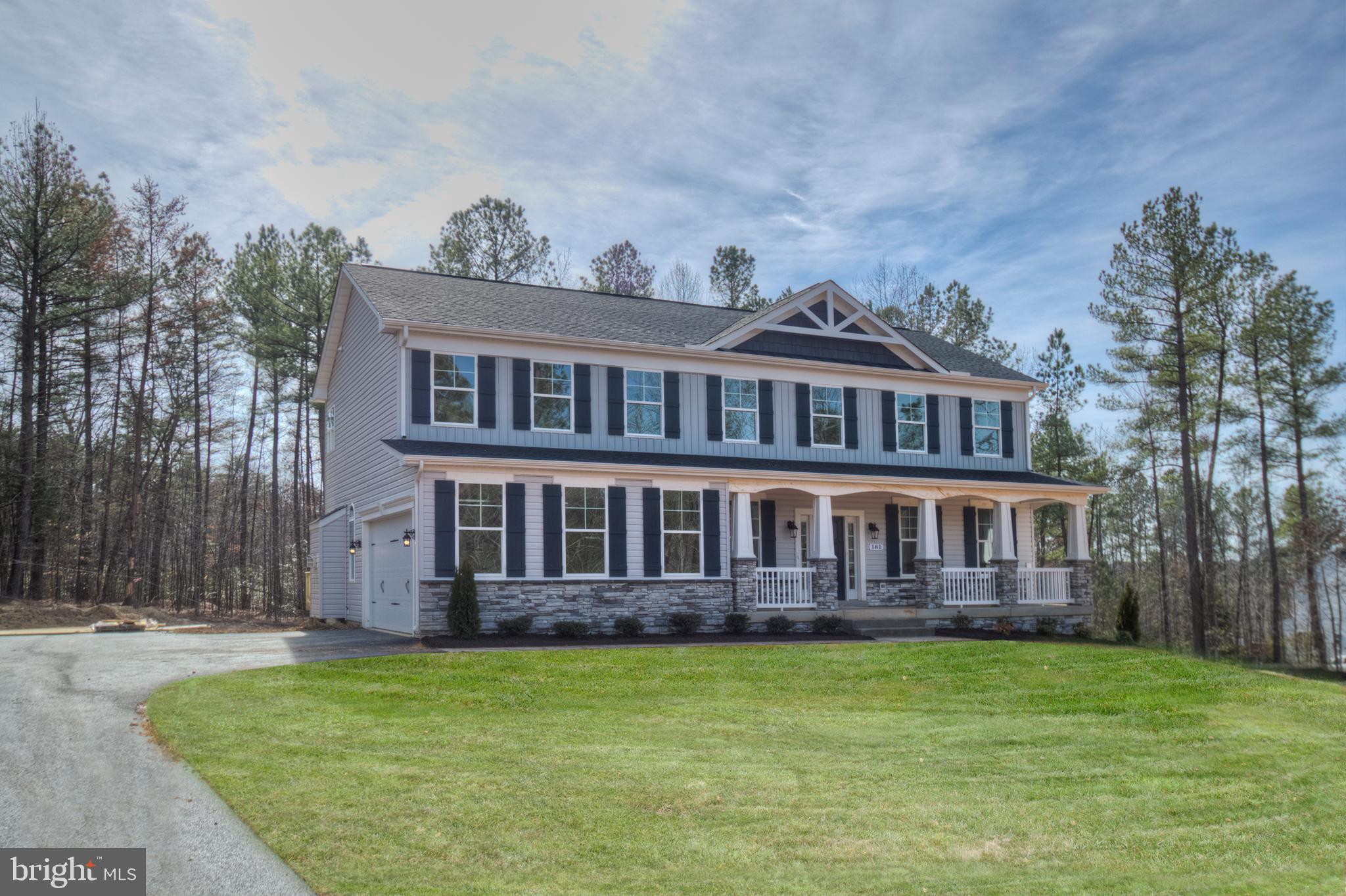 A beautiful Colonial with Craftsman Front Stone Columns front porch and two car side load garage awa