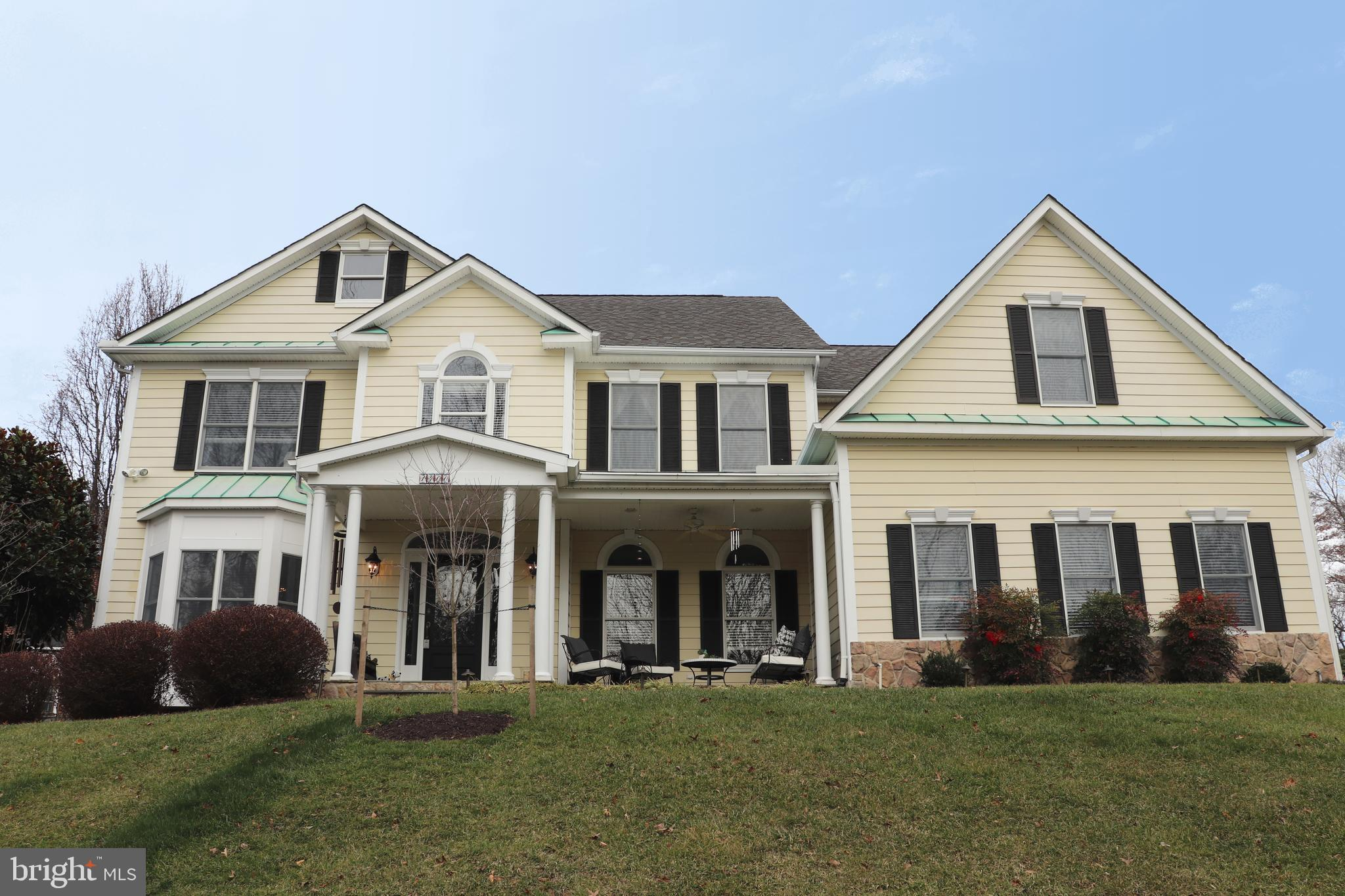 Stately and southern colonial with welcoming front porch and vaulted ceiling screened in porch locat