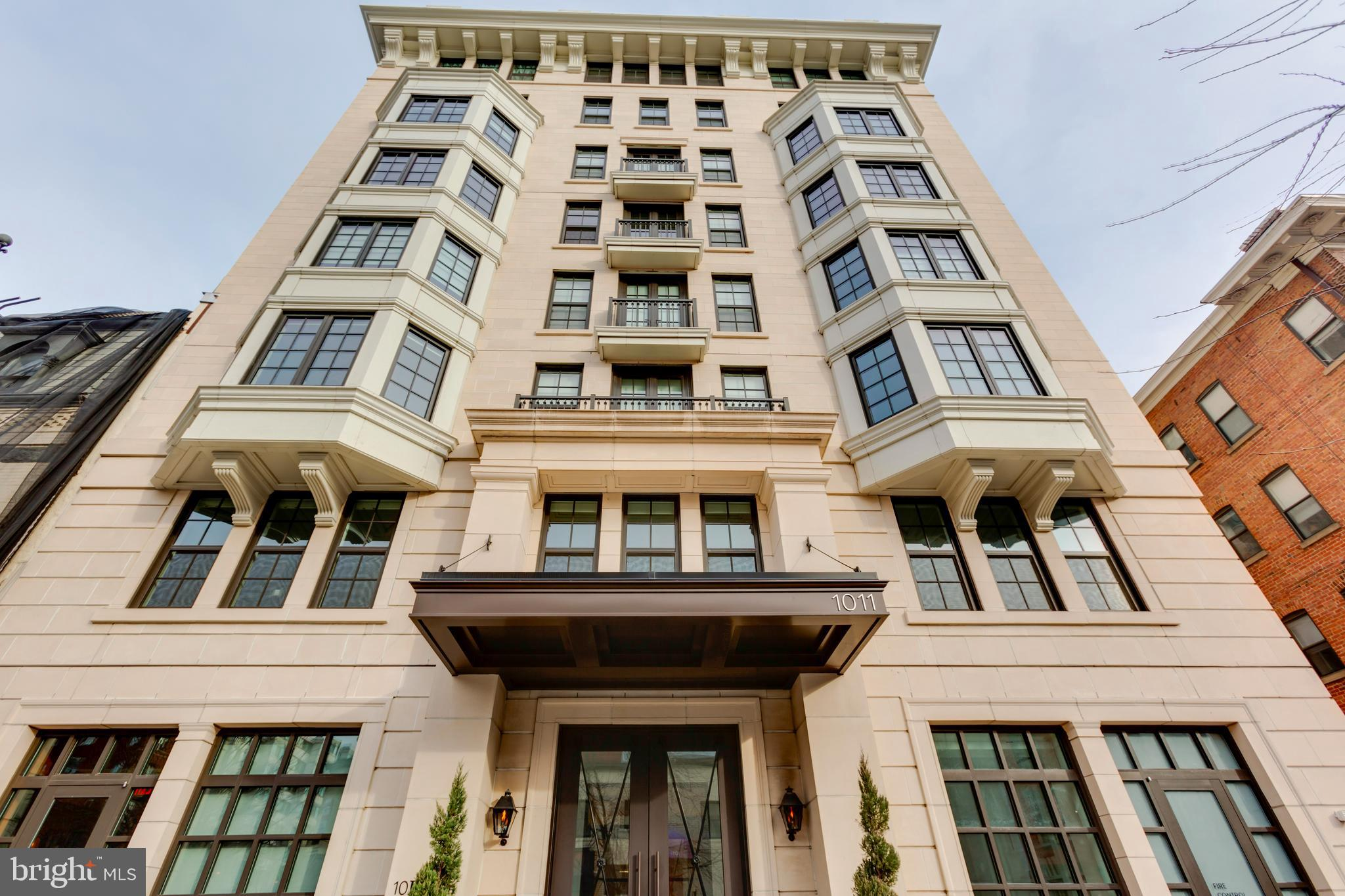Light-filled contemporary condo in luxury building with sleek kitchen, oversized windows, hardwood f