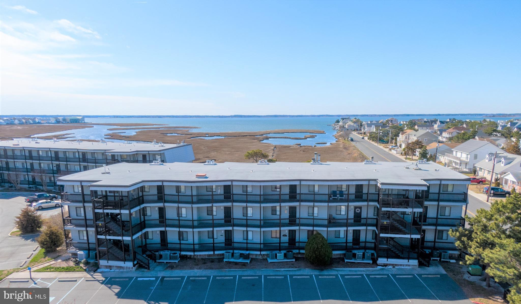 $2,500 seller credit being offered toward your dream beach kitchen w/ acceptable offer!!! Stunning bay views, huge community pool & only two blocks to the beach, you can have it all!! This well kept home has never been rented & is being offered fully furnished.  Relaxing decor with updated laminate flooring and even has a wood burning fireplace to enjoy in the offseason.  New exterior A/C installed this year. Community has ample parking and is professionally managed. Come see this view for yourself!