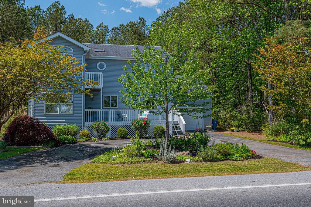 This updated home has space for everyone.  It is located in the heart of amenity rich Ocean Pines; a quick walk or bike ride to the Yacht Club,  Marina, boat ramp, pools, and weekly farmers market at White Horse Park.  Spend the  Summer months on your large front deck and enjoy a view of Pintail Park and the canal just across the street.   Or the back deck- overlooking your fenced rear yard- the perfect space for outdoor games, grilling, and relaxing in the sun.  Inside you are met with an open kitchen and living room with updates throughout.  The rest of the first level has a functional flow great for entertaining or spreading out and enjoying some privacy.  The 2nd living room has a fun walk through bar space/butlers pantry, AND there is a guest room and full guest bathroom close by.  A little further down the hall is the master suite with spacious walk in closet and a little sunroom that is perfect for your plants,  exercise equipment, reading nook,  etc.  The  master bath just underwent a complete renovation and has a soaking tub, tiled shower and floor as well as double sink vanity.    Upstairs are two additional large bedrooms and a  full bathroom as well as multiple walk in attic storage spaces.   The circle drive means room for multiple vehicles,  AND the wooded lot next door offers privacy.   Video tour coming soon!