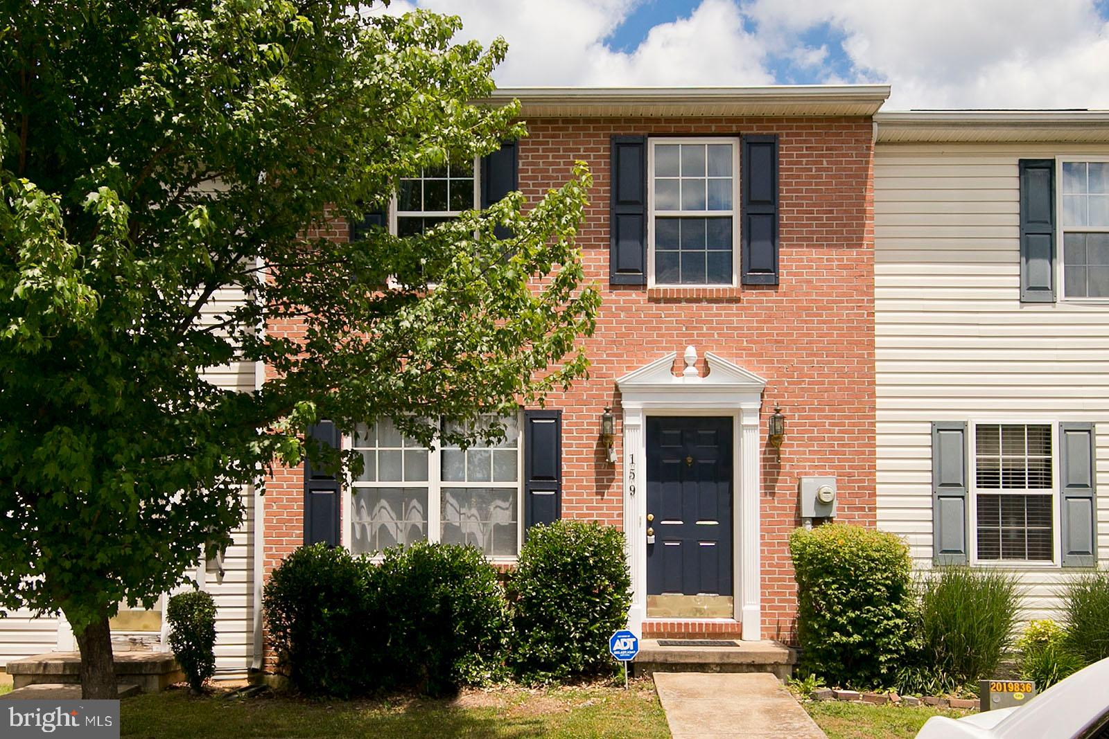Brick-front townhome  with spacious fenced backyard, attached storage shed, and deck.  Main level in