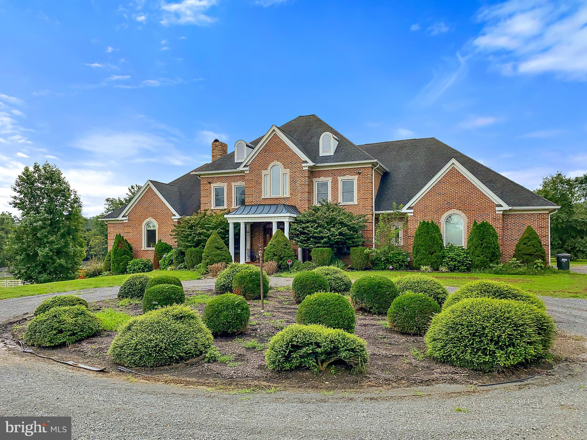 Welcome Home to 16866 Hamilton Station Rd, Hamilton VA.  This All Brick Manor Custom-Built Home is Perfectly Situated on 10 Acres with its Onsite Vineyard, a 6-Stall Horse Barn with High-Tensile Polymer (HTP) Fencing, Pastures, and Offers Amazing Views and Privacy with Extensive Installation of 240 Western Red Cedar (Cypress) Privacy Trees Around the Property. NO HOA & High-Speed Internet is Available!   This Gorgeous Home Includes 6 Bedrooms with a Main Floor Owners Suite and On Suite Bathroom, 5 Full Bathrooms, Grand Foyer with Marble Flooring and Beautiful Curved Staircase to Upper Level, Formal Living and Dining Room, Office / Den, Large Kitchen with Upgraded Stainless Steel Appliances and Island with Granite Countertops, Eat-In Kitchen Area that Leads to the Large Deck Overlooking the In-Ground Swimming Pool, Family Room, Main Level Laundry Room, 3 Fireplaces, and 4 Car Garage.  Custom Detail Work Throughout this Home Includes 9 ft. Ceilings, Crown Moldings, Chair Railings, Window Treatments, Hardwood Floors, Marble Foyer, Granite Countertops in Kitchen and Bathrooms and Much More.  Property Includes an Open Canvas for its New Owner to Customize the Unfinished Basement Area (3,331 Sq. Ft) for Additional Living Space with Walkout Access to Large Back Yard and has 2 Rough-Ins for Additional Bathrooms or Possible Lower Level Living Suite.  Portion of the Unfinished Basement Area Converted into the Properties Own Wine Making Facility for Harvesting Approximately 1.5 Acres of Beautiful Vitis Vinifera Vineyard to Produce Your Own Cabernet Sauvignon and Cabernet Franc Wines.  Home Offers Energy Efficiency with Geo-Thermal Technology for Heating and Cooling that Provides Overall Lower Cost for Utilities.  Outdoor Structures Include a 6 Stall Barn with 2 Large Pastures, Run-In Shed, High-Tensile Polymer (HTP) Fencing, and Large Equipment / Storage Shed.  This Home is Move-In Ready. Conveniently Located Within Walking Distance of the W&OD Walk / Bike Path, Nearby Shoppin