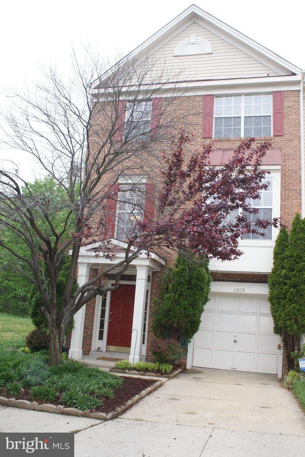 Luxurious 3-level brick-front end-unit townhouse with garage and deck backs to woods and open common