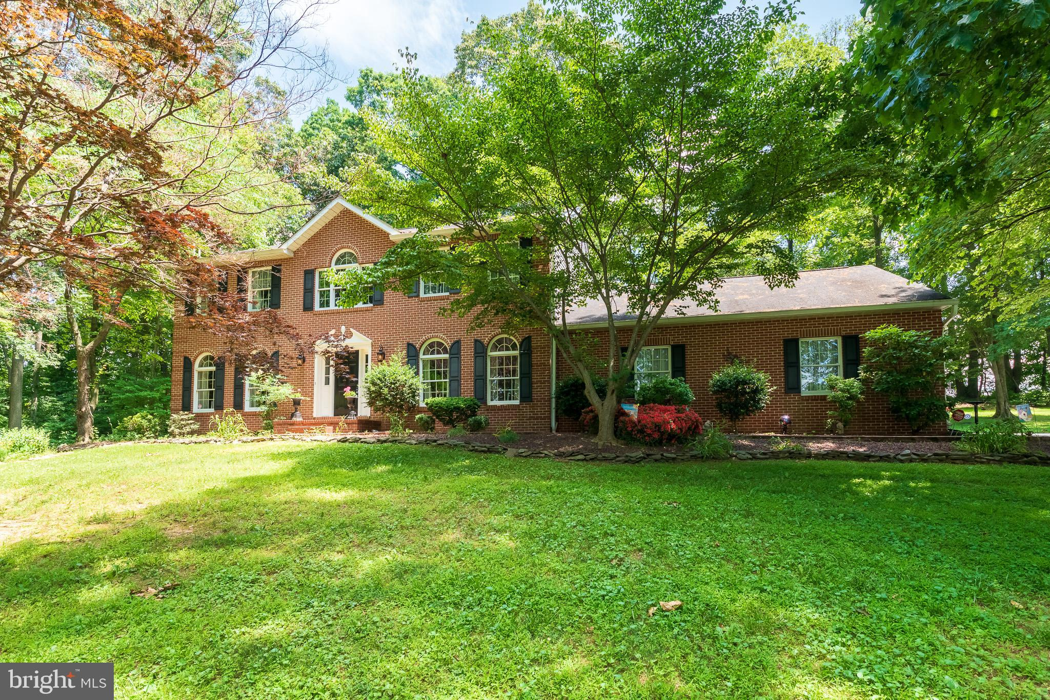 Stately brick front 4 bedroom 2.5 bath colonial with oversized 2 car garage is located on a beautifu