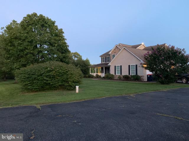 Custom built colonial stone / stucco three story home with wrapped around porch located in quite nei