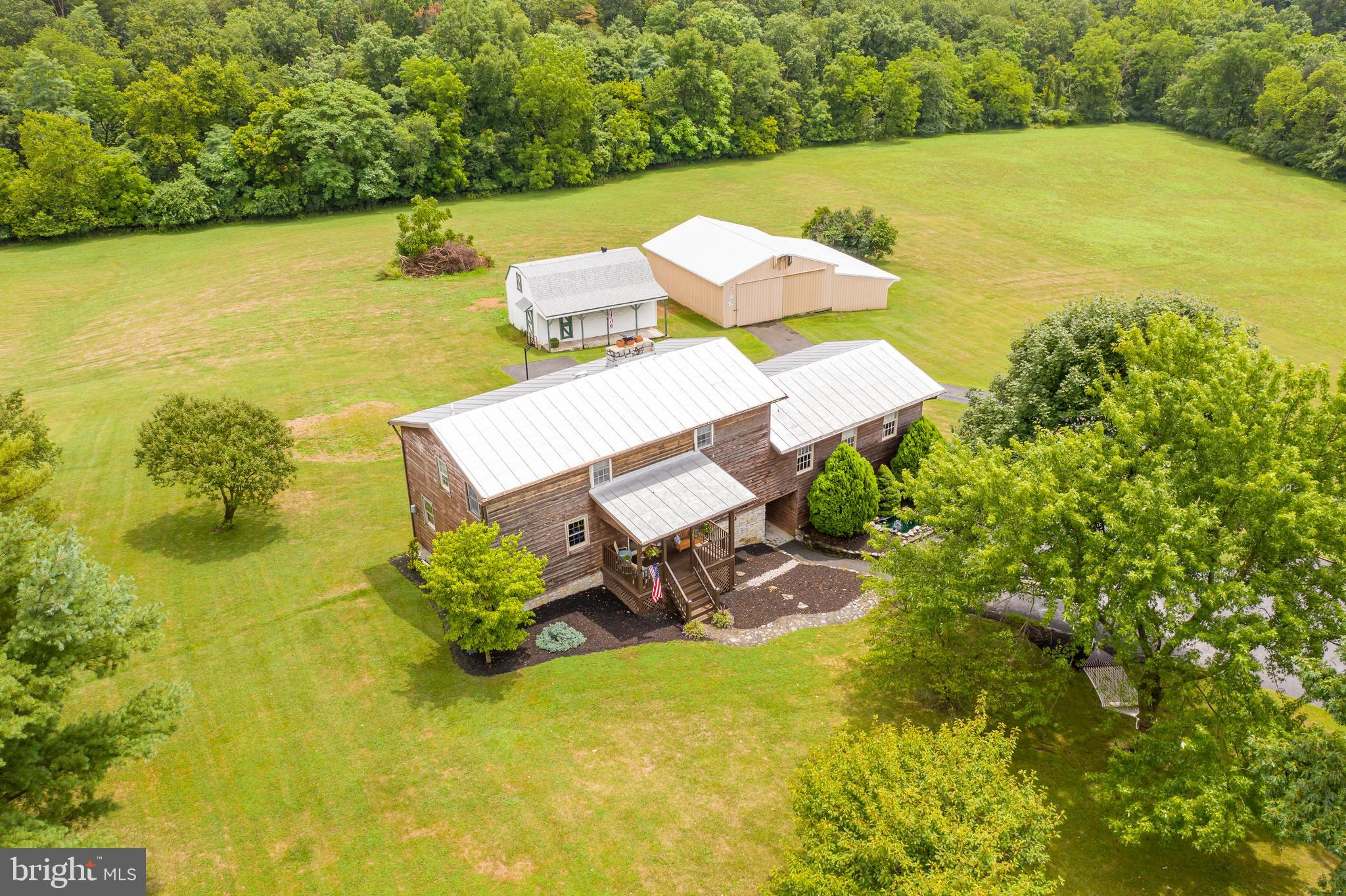Who is ready for 8.25 acres of UNRESTRICTED land? This home offers 2 large outbuildings; one could be a home office and the other is a pole barn with a lean to for horses or cows. Lots of room for chickens!! The back yard is perfect for an in-ground pool as the septic field is behind the outbuildings. Once inside, you will step into yesteryear with original pine floors throughout the main and upper levels, hand hewn logs (which came from two cabins in Harrisonburg, Va) with chinking, wooden beams, and a beautiful stone gas fireplace.  The farm house galley kitchen is adorable; there is a den off one side of the kitchen and a dining room on the other.  There is a TV room and a great room which is being used as a bedroom.  There is a full bath on the main level.  Upstairs there are 3 bedrooms and one full bath.  Downstairs there is a half bath, office, laundry room, and the rest of the basement can be finished as desired; there is a gas wall unit. The basement leads to the oversized 2 car detached garage. There is a metal roof on the home and pole barn and the asphalt shingles were installed in 2018 on the other outbuilding.  There is a 2 zone heat pump; the upstairs unit was installed in October 2019 and the main level unit was installed in 2018. The propane tank is owned.  The owners have Direct TV and HughesNet can provide  internet service there. This home is a real find so bring your animals, four wheelers, etc!!  Located close to Route 81 near Winchester, VA, Berryville, VA, Bunker Hill, WV, Charles Town, WV and less than an hour from Northern Virginia.