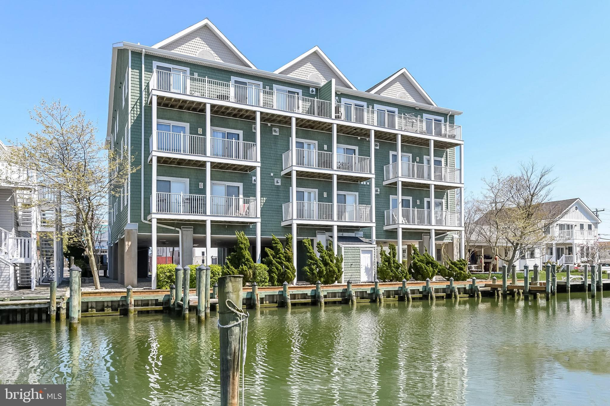 This turn-key, open concept, waterfront condo, in the highly-desired building, Anchors Aweigh, is just what you've been looking for! It has everything: location, views, luxury finishes, premium furnishings & most importantly, a deeded boat slip is included which you do not pay extra taxes on! The original owners, who have never rented this condo, did not skimp and thought of everything when renovating this gorgeous condo in 2017. This 3-bedroom, 3-bathroom, 2nd floor condo has breath-taking views from the balcony of the bay and even ocean views from the front entrance, which is perfect for watching the renowned Air Show every summer. There is crown and baseboard molding throughout the whole home, along with upgraded carpet in the bedrooms & living area, and tile in the foyer, kitchen, laundry room & bathrooms. The ceiling has been insulated for enhanced temperature control and energy-efficiency, (this is the only unit in the building with this feature.) Each bedroom has its own full bath with tiled showers and linen closet. Additionally, each has upgraded ceiling fans with light fixture, along with the living room, and there are two spacious, walk-in closets in the master and 2nd bedroom. The master bathroom also includes a jetted tub to relax after a long day at the White Marlin Open weigh-in, which is right around the corner. From the master bedroom and the living room,  where there is a beautiful custom cornice over the sliding glass doors, you can access the spacious balcony with composite decking & wrapped columns.  There are plantation shutters in the 2nd & 3rd bedrooms. The living room & the 2nd bedroom have TV's mounted on the wall for convenience. Below the TV in the living room, you'll find a gas fireplace covered with glass doors and the gas for the fireplace is included in the condo fees! If you like to cook, you will totally love the kitchen that is full of energy star, stainless steel appliances, as well as granite counter tops and recessed lighting. There is a breakfast bar with stools, along with a full dining room set that seats 6, so the whole family can dine in. You also have a large pantry/storage closet off the kitchen.  Take note of the extra large square footage this unit has to offer as the units on each side of this are smaller. If you want a break from cooking, there are so many great restaurants within walking distance. It's also very convenient having CVS right across the street for quick shopping. But more importantly, the beach & boardwalk are just 3 blocks away! You will never need to worry about parking in this prime location, as there is an assigned parking spot, plus 5 others available on a First Come, First Served basis, underneath the building, and plenty of street parking. You also won't have to lug bikes, beach chairs or sand up to this immaculate home, as there is a storage room, bike storage & an outdoor shower. There are only two boat slips for this building, and this unit includes one of them, recently having the dock boards replaced, and can house up to a 25 foot boat.  The lobby is secure and has an elevator to access the 2nd floor, where the condo is located. The front door has a keypad, along with key entry for easy access. For peace of mind, the Sellers are paying for a 1-year Home Warranty. What more could you ask for when you have all of this at the Beach! Take a look at our virtual showing first and then schedule your showing today to appreciate all of the beauty that can be yours!  To maintain the beauty of this unit, kindly remove shoes upon entering!