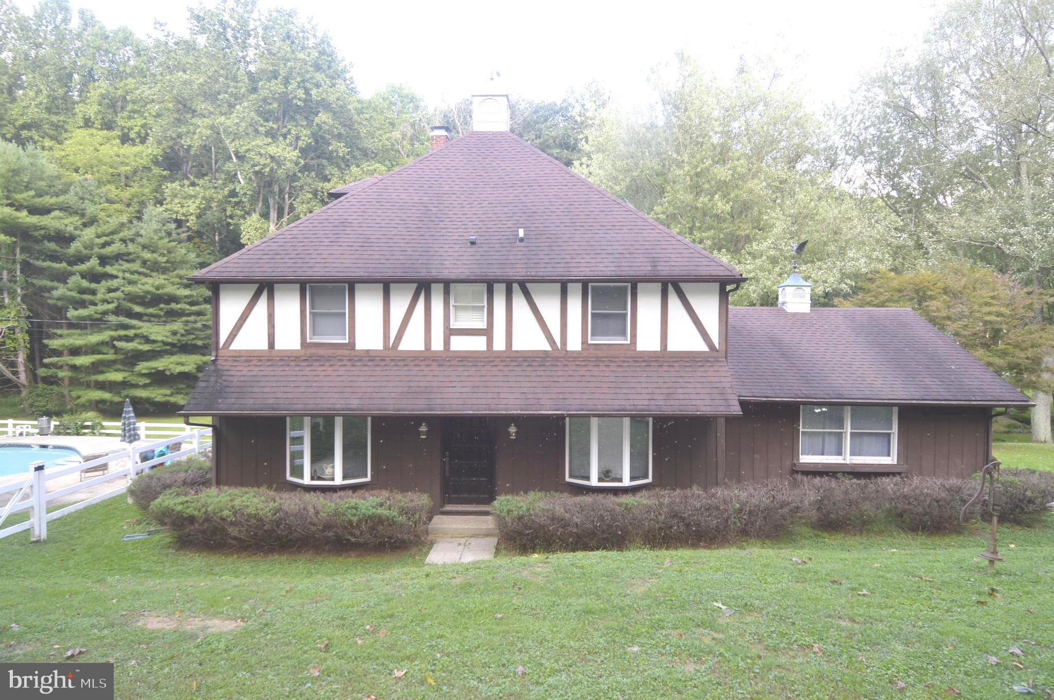 Beautiful tudor home on 8.5 Acres. This 4 bedroom 2 full bath offers very spacious and open rooms. B