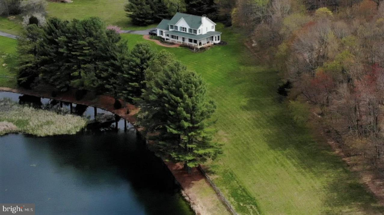 'CATTAIL POND' - CLASSIC TWO-STORY FARMHOUSE SITUATED ON 3+ ACRES OVERLOOKING 'CATTAIL POND'.  Waterfront property located in Baltimore County's desirable Hereford Zone.  Idyllic living in a spectacular setting best describes this beautiful 3 BR, 2.5 BA home and grounds. Surrounded by woods in the back, three acres of grounds, wrap around porch, meandering brick sidewalk and low maintenance gardens. Formal Living Room, Dining Room, 2-story entry Foyer, and Family Room adjacent to a large Country Kitchen complete with a Breakfast Nook that overlooks the pond and property.  Large wood burning fireplaces in both the Family Room and Master Bedroom offer wonderful ambience and warmth when the temps are cool.  Hardwood floors and floor-to-ceiling windows throughout the main floor.  Three oversized bedrooms upstairs including a large master bedroom suite complete with wood burning fireplace, spacious bathroom and large walk-in closet. Master Bathroom offers a large soaking tub, separate shower, and two sink vanity.  Laundry Room is located on the main floor complete with laundry chute  from the 2nd floor that saves both time and energy.  Two car oversized garage.  New paint inside and out (2020) and new roof (2017). Basement is unfinished with rough-in for a bath. The kitchen and bathrooms could benefit from updating, offering the new owner the opportunity to customize all to your taste while making the home more affordable.