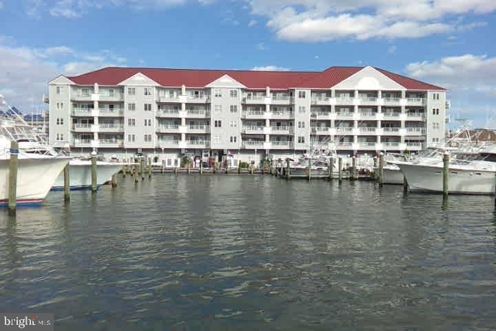What a buy! A chance to own a beautiful bayfront condo with 2 very large Boat slips capable of docking 50-60 ft boats. Use them or rent them, great income stream.  Approximate rental income for 2 slips and condo $35,000.00 per year. This beautiful direct bayfront condo has a large balcony over looking marina, pool, and gorgeous sunsets.  Recently new stainless steel appliances including a wine cooler, new HVAC in 2016,  and custom laid wood flooring. It features 2 very large bedrooms and 2 baths, meticulously maintained and exquisitely decorated in model home condition with new tempurpedic and posturepedic beds. There are 2 assigned parking spaces in gated garage. Community has new pool, piers, bulkhead and elevators.  From this location you can park your car upon arrival and walk to everything in 5 minutes including, beach, boardwalk, inlet,  waterfront restaurants pubs and  bars, all kinds of watersports and so much more! Be the first to view this incredible property. First viewings October 15th