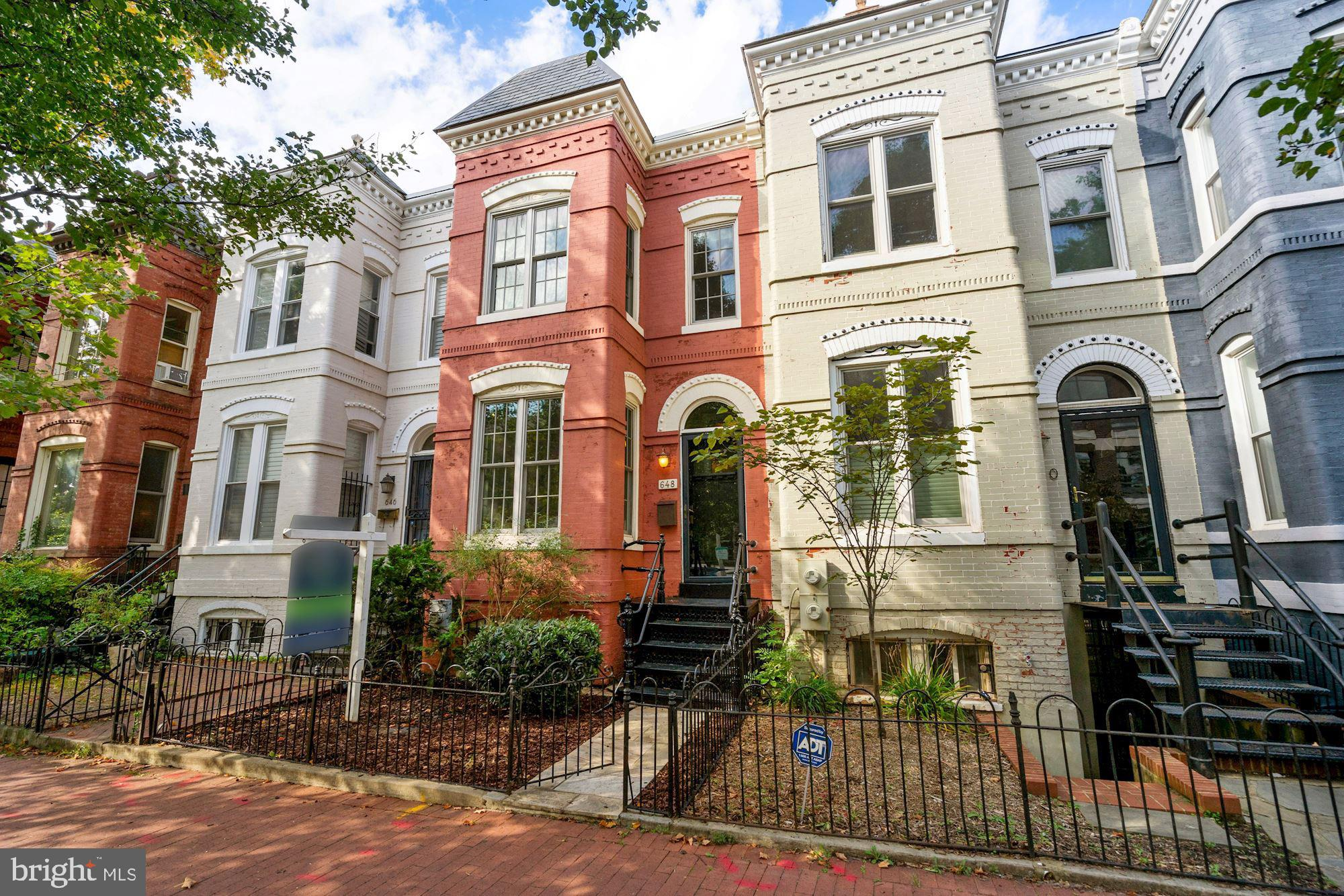 Welcome Home to Capitol Hill! This newly available, federal style, bow-front row home at 648 G Street NE is conveniently located between Stanton Park and the H Street corridor. It's just a few short blocks from Union Station, Whole Foods, Giant, Union Kitchen Grocery and some of the best shops and restaurants in DC. A 3-level, all brick home, it features 3 bedrooms and 2.5 baths with secure off-street parking and a deep backyard. An entertainer's dream, you can host friends and family for appetizers before heading out on the town. Or accommodate a large fete in your home's main level and backyard.  As you enter the front gate of this home, you'll appreciate its charm. From its classic entry foyer and 9-foot ceilings to its wood-burning fireplace, hardwood floors and sunny bow-front windows, this home is sure to please. With an open living and dining space, the flow is terrific. Just past the powder room is the renovated shaker-style kitchen with newer cabinets, stainless appliances (including a gas range with double ovens), quartz counters and tile floor. If your party is large enough or if you'd just like to dine al fresco, enjoy the spacious stained deck and patio just off the kitchen. Whether it's to barbecue, enjoy your morning coffee or you just need a break between zoom calls, this rear garden is the perfect feature. And just beyond the back fence is secured parking. The rolltop garage door was installed in 2017. Upstairs with hardwood floors continuing throughout, you'll find a large Owner's suite with sunny sitting space, plentiful storage and a renovated en suite bath with heated floors, frameless glass shower enclosure and dual sinks. There are 2 guest bedrooms as well and an updated hall bath with jetted tub. The lower level houses the laundry area. It is unfinished and ready for your designs.  Beyond its charm, this home has practical and money-saving features such as newer windows, updated roofing, tankless water heater, a French drain, a new dishwasher