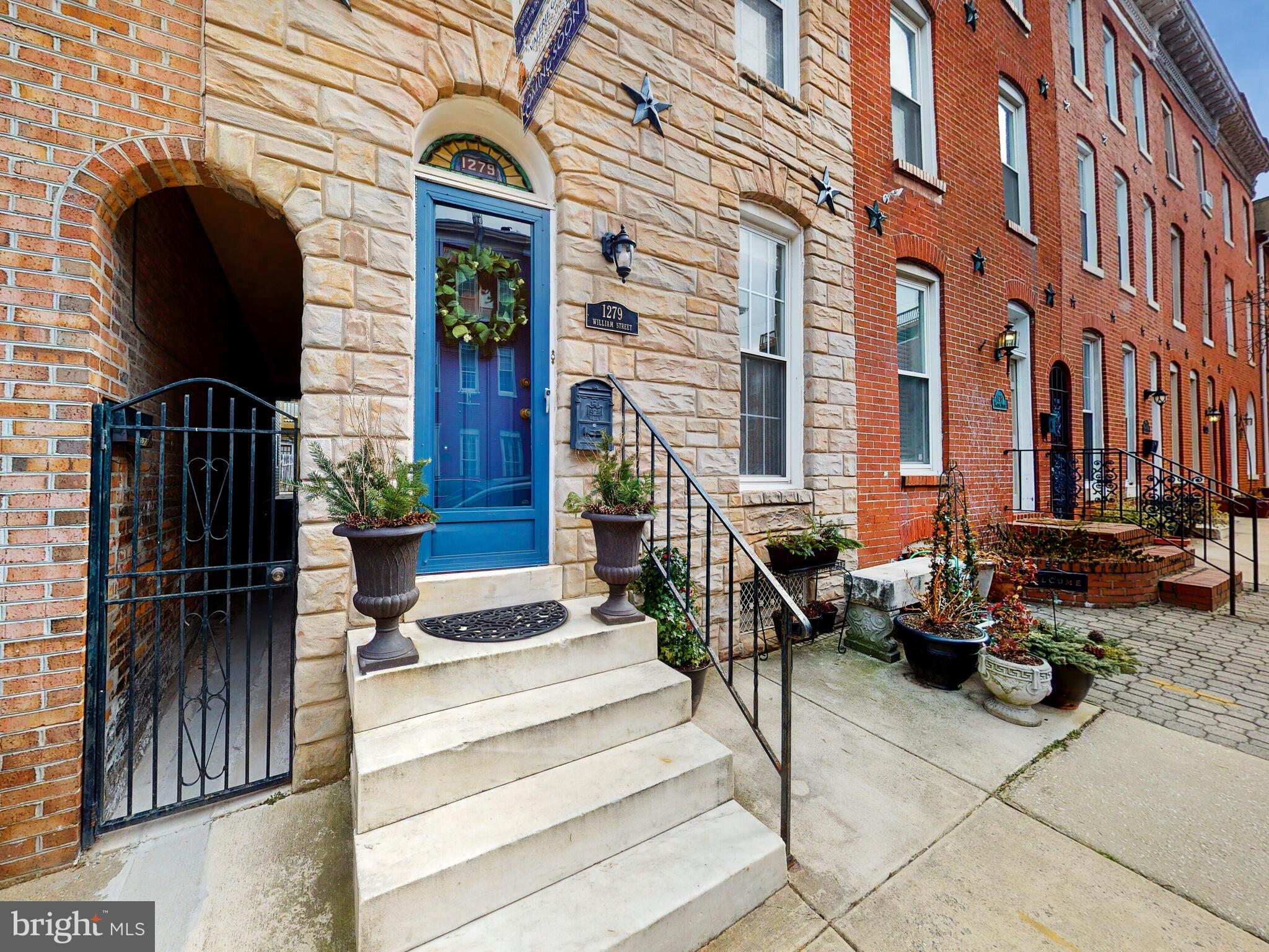 This quintessential Federal Hill home located on one of the area's most desired streets features large sun-filled rooms accented with extensive millwork, exposed brick, and hardwood floors with inlays. The main level conveys 9 ft. high ceilings; marble fireplace; powder room; chair rail and picture frame molding; and built-in cabinets for storage. The center hall's exterior door opens to breezeway which provides convenient access to both front and back of home. Formal dining room leads to a huge kitchen that offers tons of cabinets, two sinks, and granite counter tops with large prep space for cooking. Second floor boasts two large bedrooms, both with en suite bathrooms; walk-in closet; washer & dryer. Walk up to the third floor where you'll be in awe of the bright sunroom with too many windows to count. Perfect for entertaining or relaxing, the third floor also features a wet/dry bar wired for surround sound; another huge bedroom and en suite bathroom; and French doors leading to the first spacious deck. Follow the interior spiral staircase leading to loft space that opens up to an another rooftop deck where you'll experience 360-degree skyline views of the city and hear the roar of the crowds from M&T Bank Stadium and Camden Yards (no better house for game days!). Dual zone HVAC, tons of basement storage, Vivent security system throughout entire home, and parking pad in back. Quick walk to Federal Hill & Riverside Parks, downtown attractions, Cross St. Market, and some of Baltimore's best bars and restaurants.