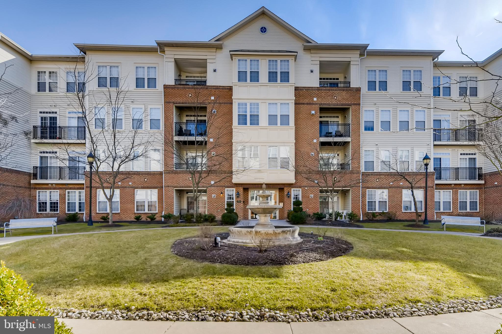 Now Active! Welcome to this gorgeous, sun-filled unit in the active adult community of Ellicott Hills. With soaring nine-foot ceilings throughout, this spacious two bedroom, two bath condo has it all. Includes an electric fireplace, sunroom, eat-in kitchen, separate dining room, and laundry room with storage space. The guest bedroom features built in shelves, a huge closet, and a delightful Juliet balcony. Recently remodeled guest bathroom boasts stylish vinyl plank flooring. The generously-sized primary bedroom includes two huge closets, an ensuite bath with an extra long vanity with seating area, stand alone shower, and tile flooring. Relax in the sunny kitchen with granite countertops and walls of windows. The unit also includes a 7' X 5' deeded storage unit on the first floor of the building. Community features a clubhouse, outdoor pool and fitness center. Freshly painted with new carpeting, the space is ready for you to call it yours. Welcome Home!