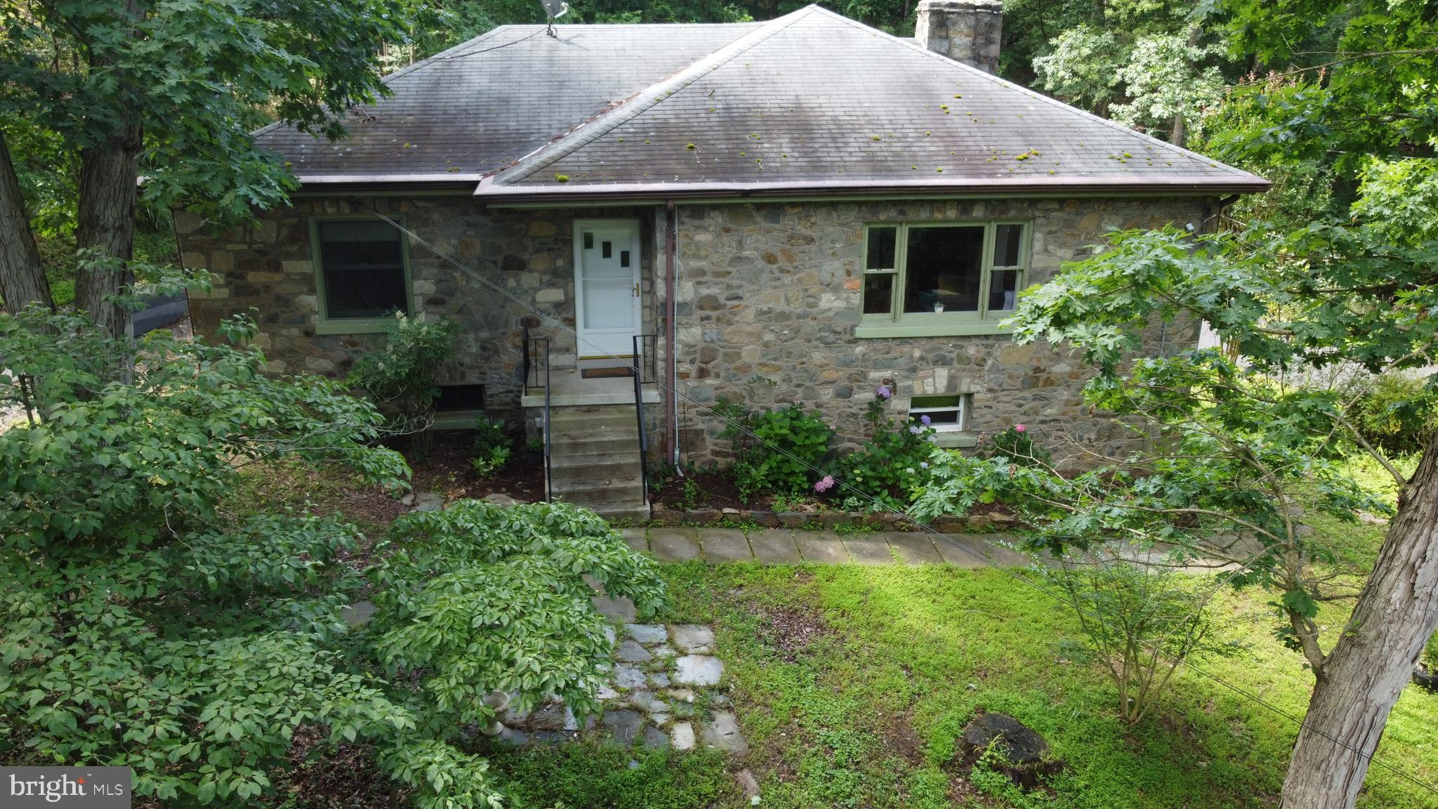 Custom stone-built home with additional income-producing cottage included with the property. Live in