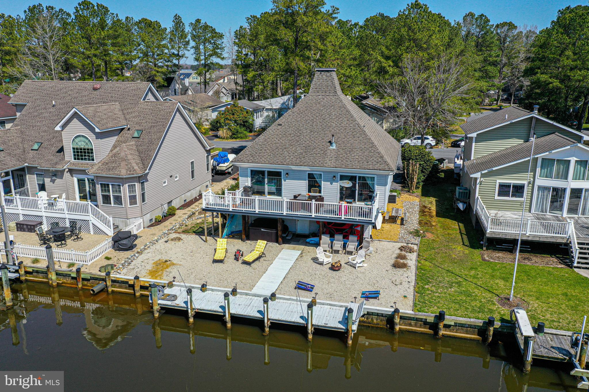 Looking for a waterfront vacation home or primary residence in Ocean Pines?   Look no further- showings start on 4/21 at 'The Teal House.'  This adorable canal front (quick access to open water- no bridges) home  with boat dockage is sold mostly furnished and ready for your enjoyment this summer.  The main level includes an open living/dining/ kitchen area with updated counters, cabinets and flooring as well as 2 bedrooms including an owners suite w/ slider out to the canal front balcony.  The upper level loft area offers a lg flex space for additional bedroom, living area, or home office.  There is ample storage in the ground floor storage area/garage as well as underneath the upper level deck for stowing paddle boards and other outdoor gear.   Located in amenity rich Ocean Pines which offers multiple community pools, golf course, Yacht Club and Marina, a beach club with private parking in Ocean City, and the many other activities (see oceanpines.org ) all just a short drive from the beaches of Assateague and Ocean City.  Sellers offering a one year HMS warranty.