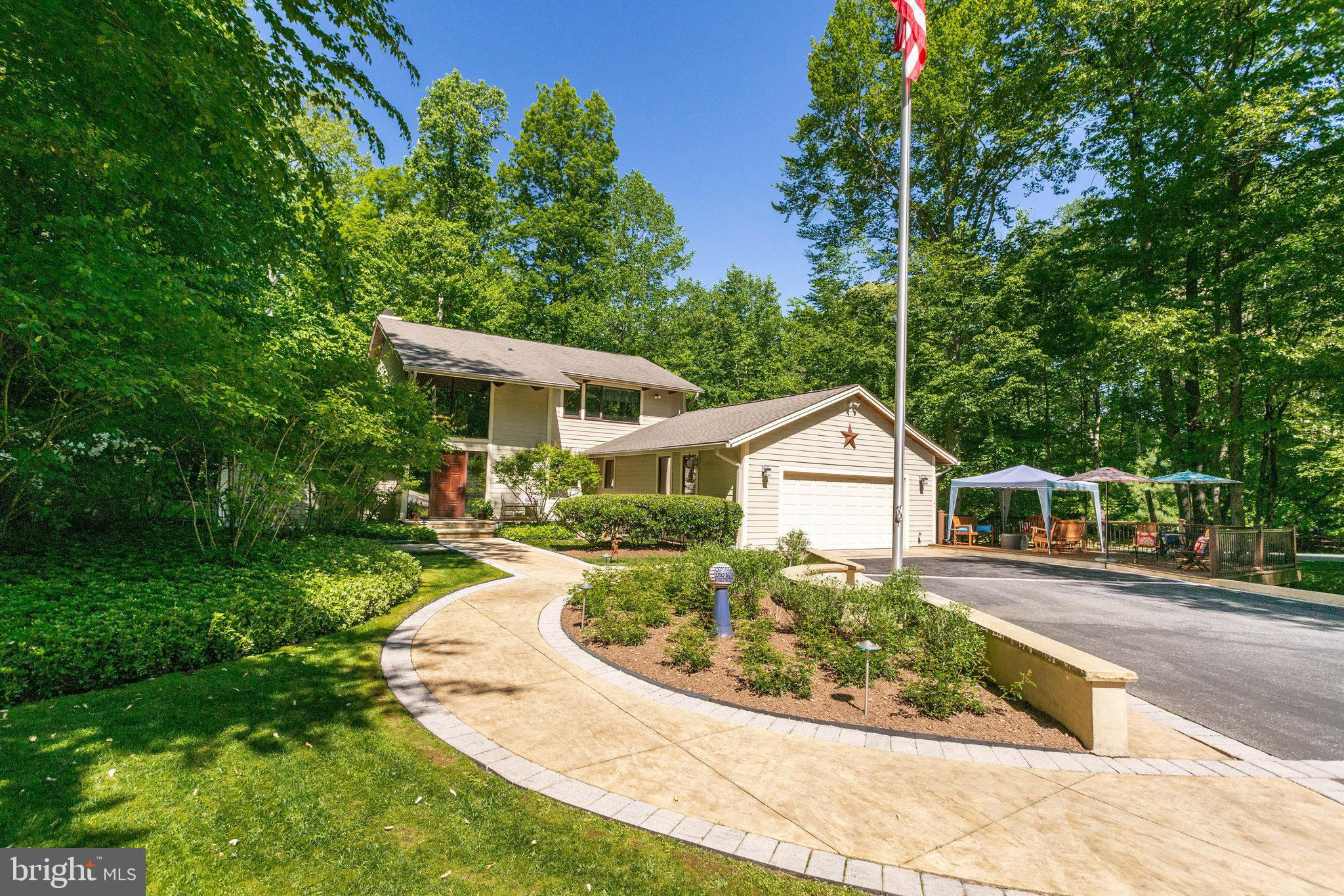This beautiful home is in the PERFECT LOCATION!  You're only 6 minutes from the mall and only 12 minutes from downtown Annapolis.  Get to BWI Airport in 20 minutes.   Yet you feel like you're far away from the city. Privacy,  backing up to trees, so you have plenty of room to stretch out and be you!  Perfect for entertaining with 2 separate decks ( one is screened and under roof) and a separate patio.  Beautiful hardscaping in the front, back and sides of your yard, yet really thought out and designed to be low maintenance.  The night scaping makes your home stand out even in the evening hours!   On the interior, walk in to gleaming hardwood floors.  You will notice right away the beautiful knotty white pine cathedral ceilings and the large architectural  windows along the back walls and up!  A large gas fireplace in your family room keeps you cozy in winter!  Your kitchen  has more modern wood cabinets with newer appliances ( 3 yrs )  and a huge island you can sit around and tell the cook how you'd like your food prepared!  Your dining room flows easily from the family room into the kitchen.  Just outside is a covered deck with festive lights hanging where conversation about everything just comes naturally.  Your primary bedroom and large bath is on the main level  as well as a separate office that is perfect  if you're working from home.  Two extra bedrooms and a full bath are  upstairs along with a sitting area that overlooks the family room.  You really notice the stunning white pine ceilings here!   Downstairs in the lower level has been perfect for the teenager/ college students who need their own space.  Partially finished with a large area for a rec room , bedroom & full bath.  They have their own private patio if they need to come up for air in between classes.  Plenty of clean unfinished space for storage or expansion if someone wanted.  There is so much more that you must see!