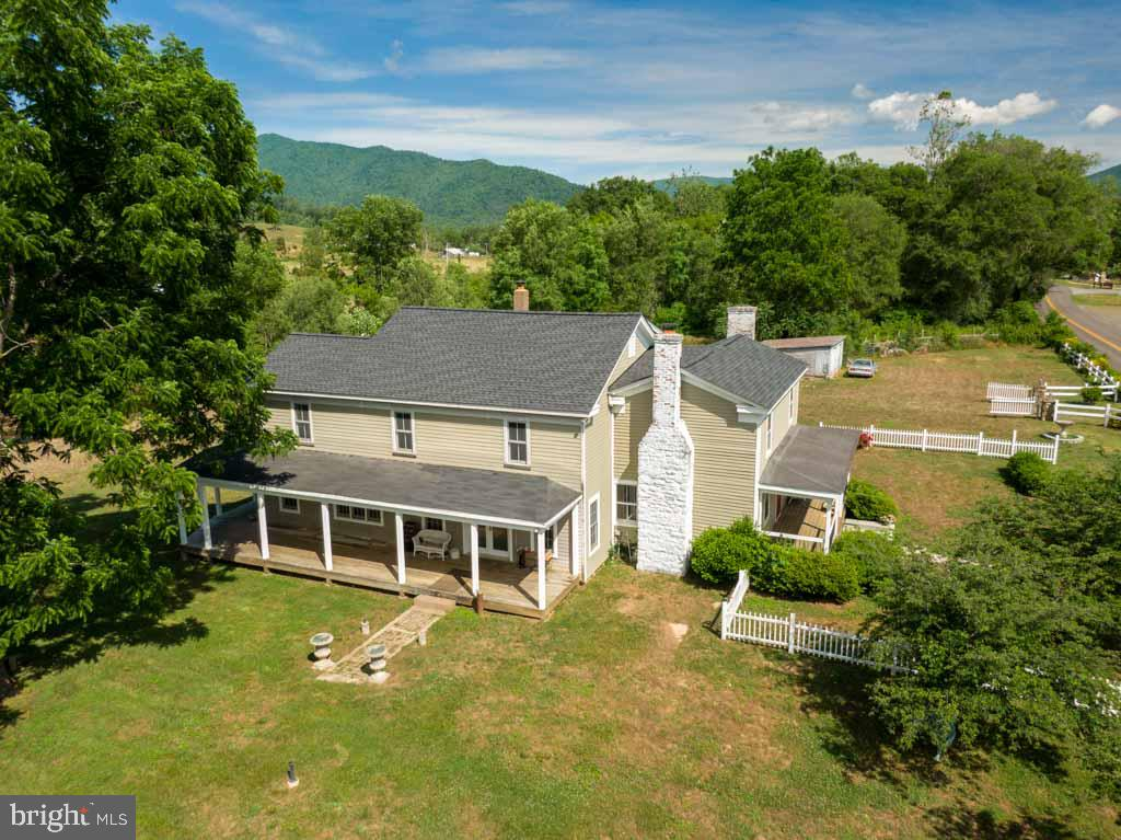 Relax and recharge in this thoughtfully restored and renovated1900 riverfront farmhouse on 2.6 acres at the foot of the Blue Ridge Mountains.  Enjoy stunning mountain views and the glorious melody of the Robinson River from every room in this bright and spacious 3698 square ft. home.   Full bathroom on the main floor, five bedrooms, three full bathrooms on the second floor (Perc'd for 3 bed)  with a jacuzzi tub and walk in shower in primary bath. Two large fieldstone chimneys flank the main house and host four original working fireplaces. (Two of which have flues for wood stoves.)  Main staircase is located off the front entrance while a second staircase is nestled at the back of the house in the charming country kitchen.  Work from home! Two separate home offices with high speed satellite internet. The main floor layout is so versatile with rooms for dining, library or den, family room, sitting or game room. Main floor laundry, walk in pantry, doors leading out to every porch and an abundance of windows to let in the birdsong and the fresh mountain air.  Upstairs you'll find 5 bright bedrooms and 3 full baths, a surplus of closet space, cathedral ceiling family room with skylights and partially finished attic space with pull down stairs. The main farmhouse has original heart pine floors and the addition has cypress and cherry hardwood floors with ceramic tile in kitchen and marble tile in side entry foyer.  Large, covered wrap around porches for entertaining and enjoying all this idyllic location has to offer.  Within steps you can trout fish in the stocked mountain river, launch your kayak or cool off in a swimming hole.  There is a two stall horse paddock on the property as well as a two bay garage with cement floor.  There is a finished shed/workshop , outfitted with 110 and 220 service which could be used as a lovely art studio.   Renovations include: legal addition in 2002 with 6x6 insulated walls and Marvin thermal windows, new roof in 2018, pressure wash and