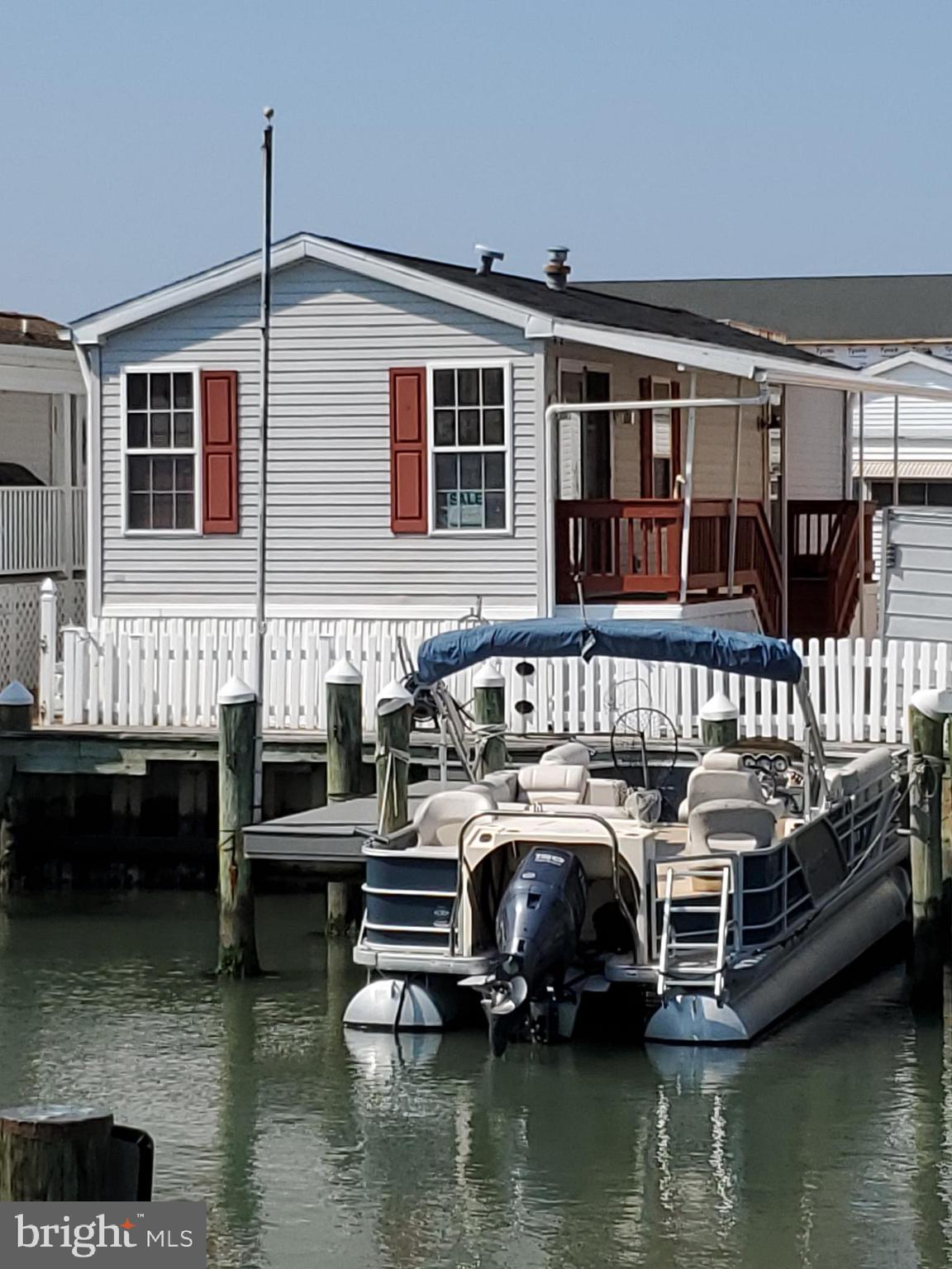LOCATION LOCATION WATERFRONT! In the Heart of OC-BAYSIDE WATERFRONT with 2  BOAT SLIPS!  EASY BAY ACCESS & CLOSE TO INLET!    2 Blocks from BEACH & OC BOARDWALK!  2 PARKING SPOTS!  This well maintained home features 2 Bedroom 1 Bath, includes open Living Area & Kitchen with Slider just steps from your deck & Boat slips.   New Carpet & Freshly Painted, Lots of Storage,  Open Deck & Covered  Awning For Entertaining!  This property is located in the Isle of Wight Co-op and is conveyed with 3,400 Shares of Stock.  Low monthly park fee of 114.00 which includes water, sewer & trash removal.  Low Closing Cost!  Won't Last Long at this Price!!  So Don't Delay and Call Today!