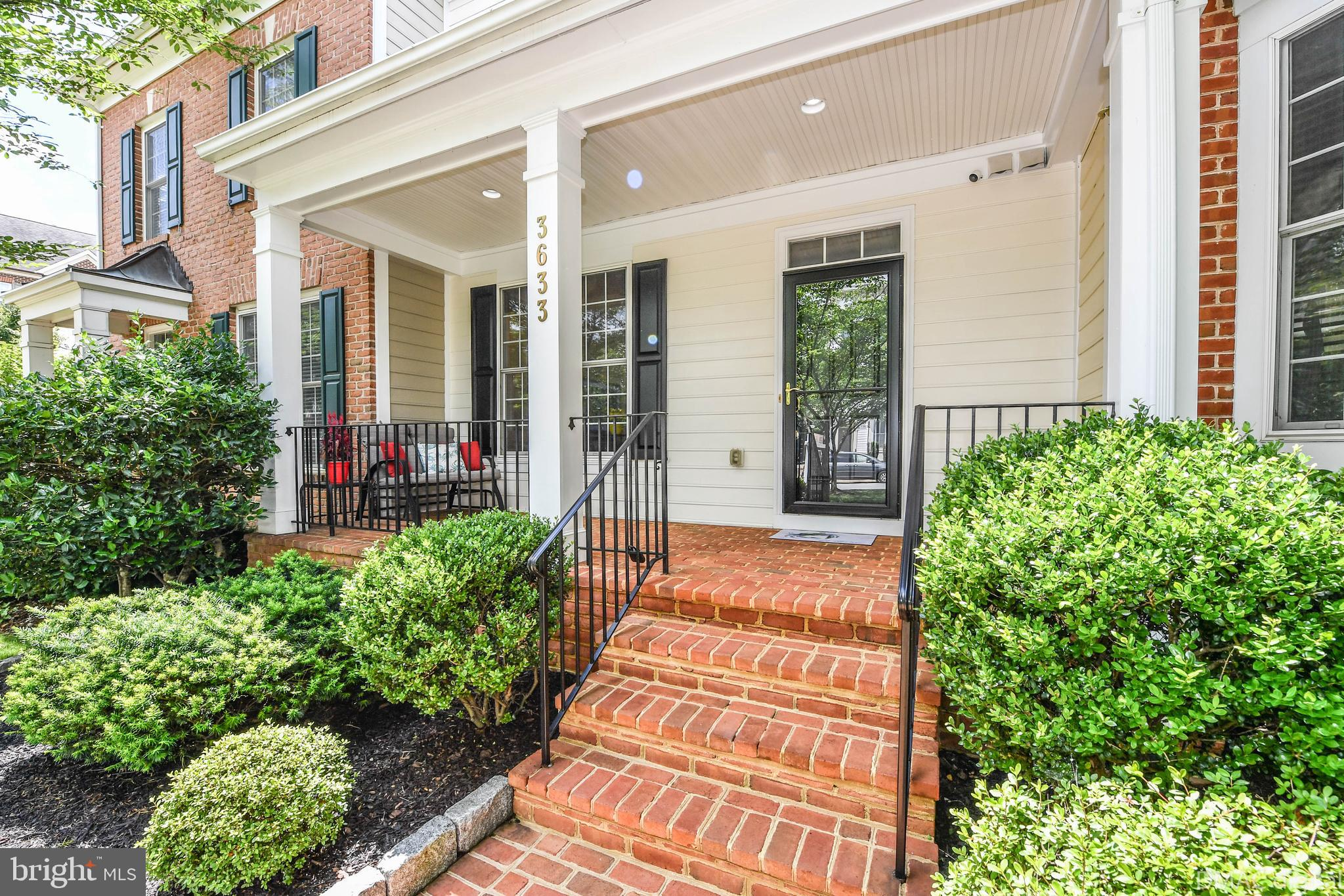 Beautifully maintained Urbana townhome with 2 car garage and comfortable front porch overlooking wid