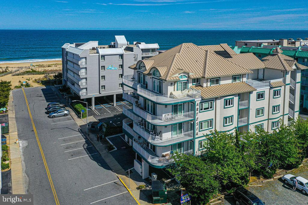 This inviting condo nestled within a coveted, low density section of the beach, is waiting for you to call it home. Sit back & enjoy the views from your wrap around balcony, with the ocean beckoning to the right and the bay summoning toward the left. It is the original, never rented, 3 bedroom 3 1/2 bathroom model unit.  Each bedroom encompasses an in-suite bathroom, with the master bath featuring a separate stand up shower & jetted tub. The condo features granite counter tops & crown molding throughout, electric storm shutters, a cozy fireplace & an expansive open living/dining kitchen area perfect for entertaining. This highly desirable building, with only 7 units, offers a Secured Lobby with an elevator, 2 covered assigned parking spaces & rooftop pool. Former model unit, never been rented. Upgraded carpet in bedrooms. Crown molding throughout unit. Plantation shutters. Electronic storm shutters Recently painted. Whirlpool tub in master bath Alarm system New sliding glass doors in 2017 Gas fireplace Building recently renovated to include new EIFS, new ceiling at parking area, new waterproofing at pool deck and elevator lobbies, and new roofing. New windows in unit Large wrap around balcony with expansive ocean and bay views Located one building back from the ocean Upgraded tile in hallway, kitchen and dining room. Wood flooring in living room. Built-in desk with granite counter and upper/lower cabinets Granite counters in kitchen, corian counters in bathrooms. 2 assigned covered parking spaces. Storage unit at 2nd floor elevator lobby.