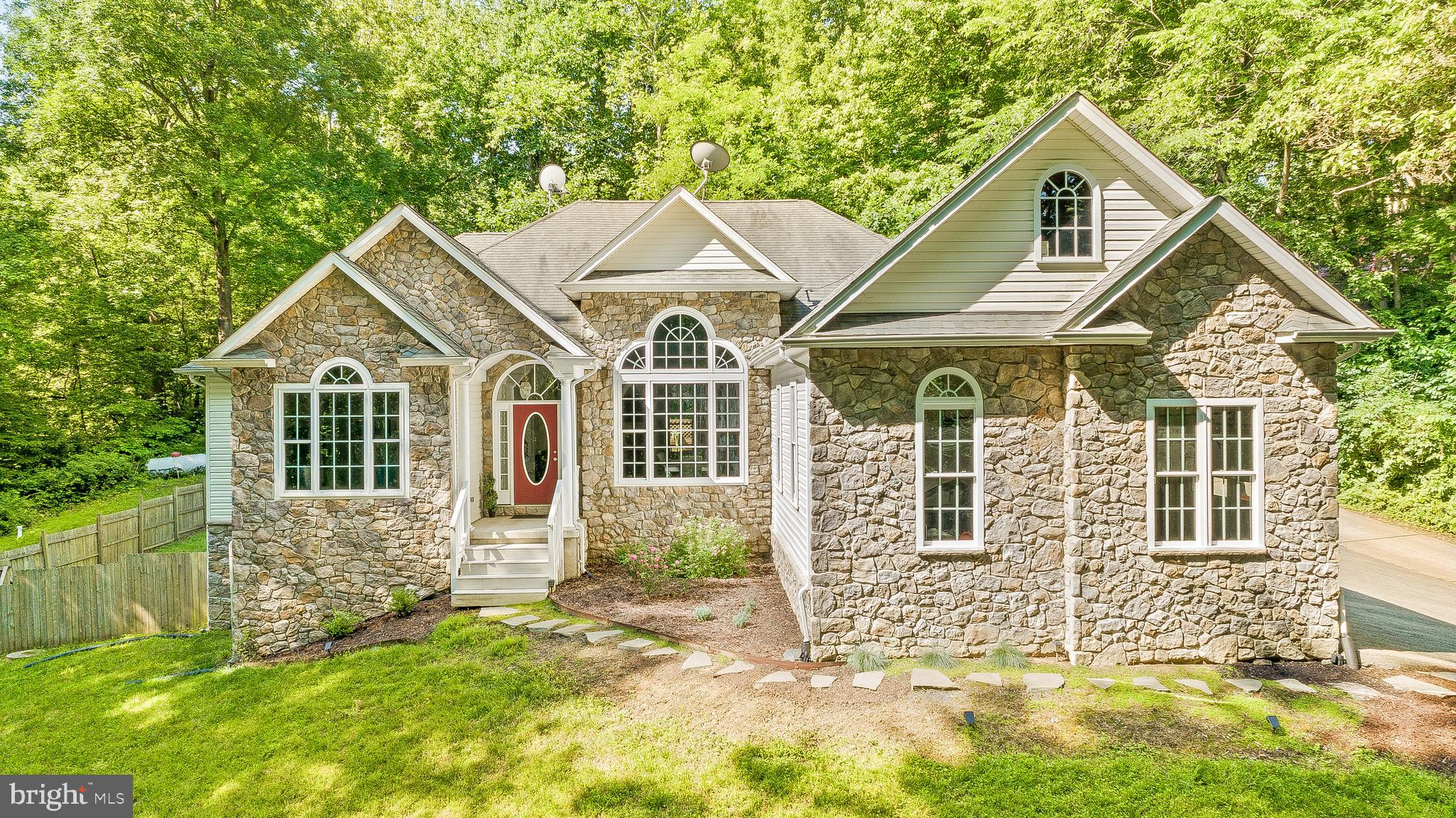 Privacy awaits with this immaculate custom luxury stone rambler nestled in the trees on its 3 acre w