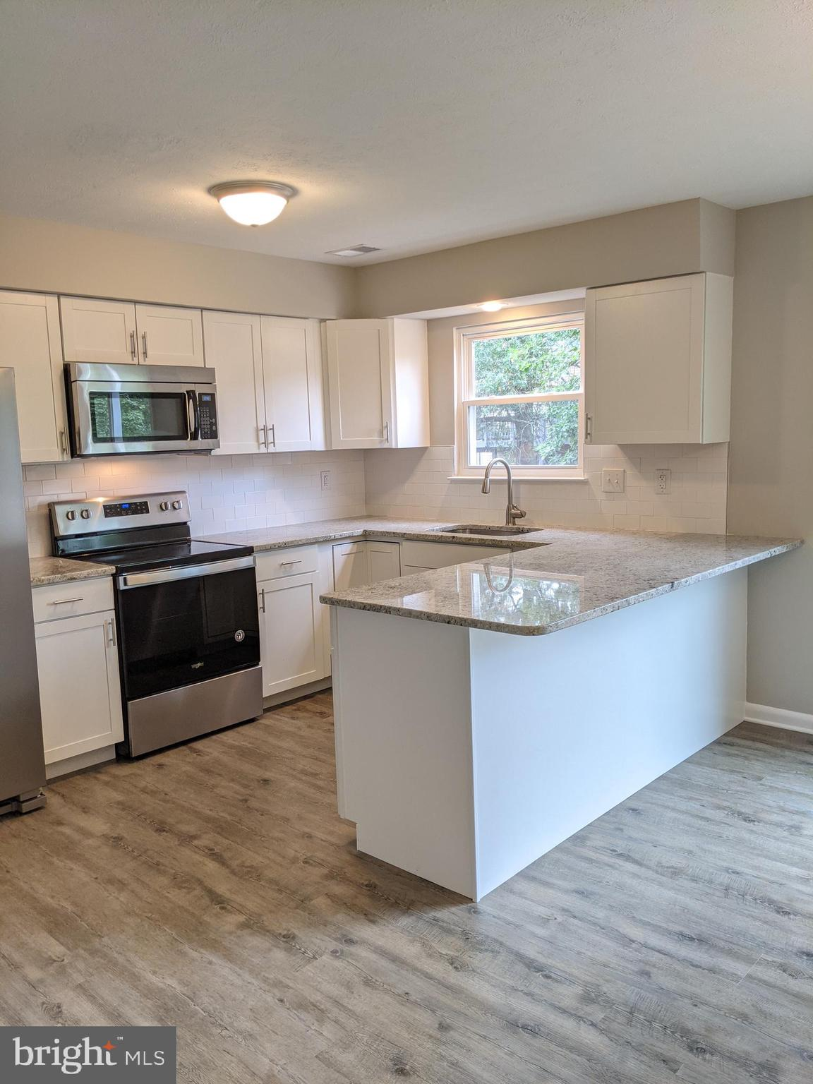 Another incredible renovation by DreamQuest Properties!  A gorgeous new kitchen with white cabinets,
