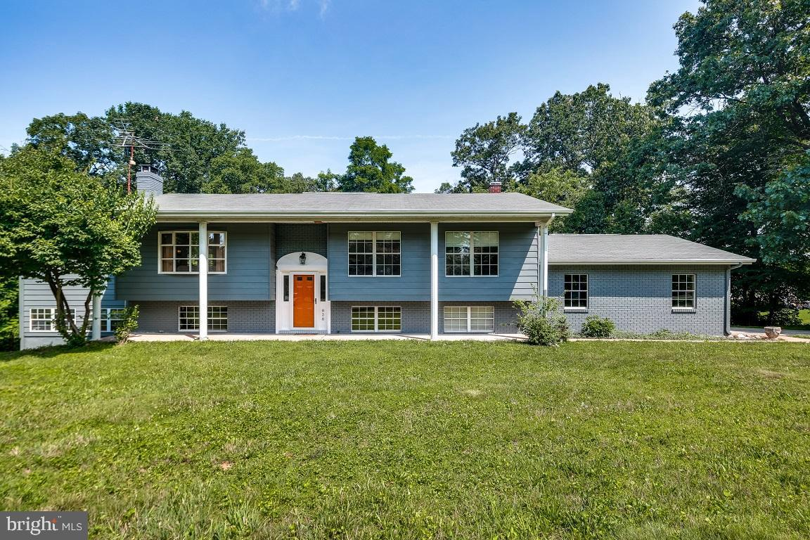 Expanded four bedroom three full bath home on a private wooded 2 acre lot. Featuring a main level wi
